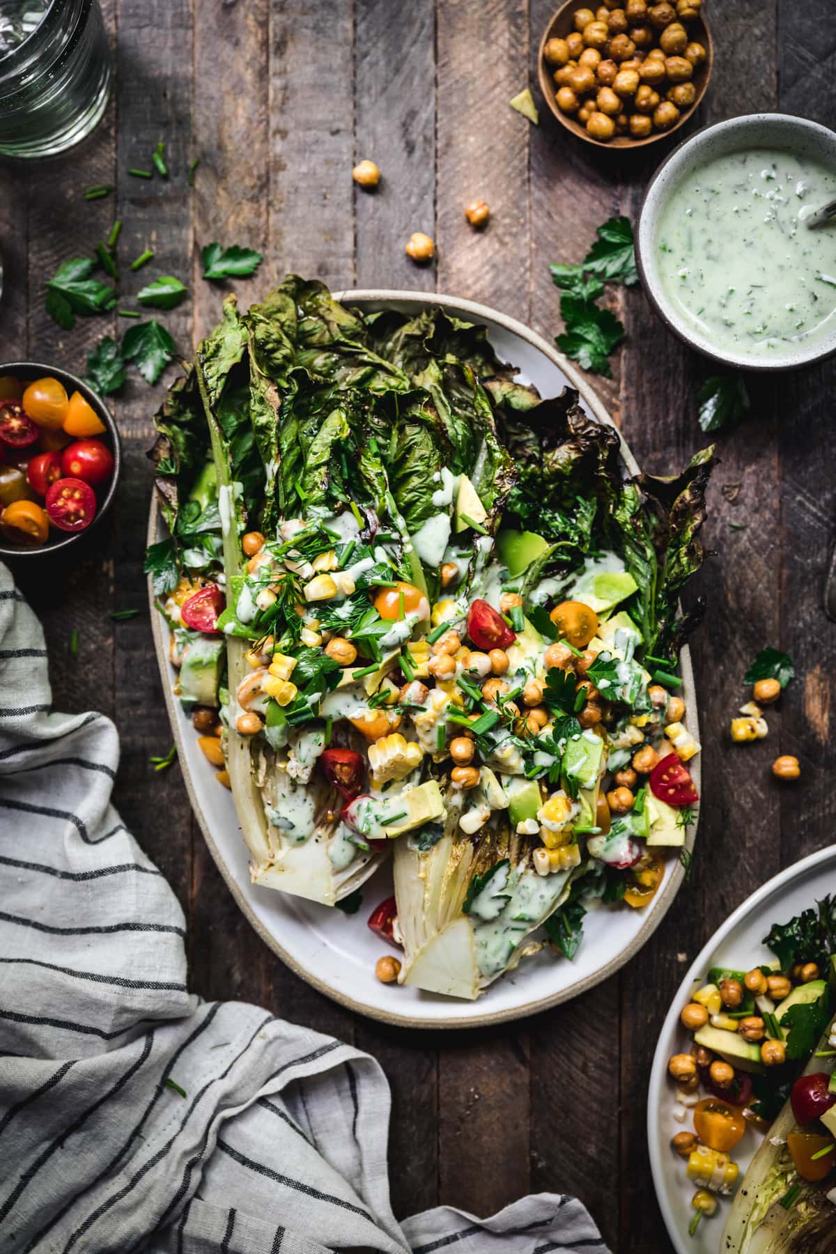 overhead of grilled romaine salad with crispy chickpeas and vegetables on an oval platter with vegan ranch dressing