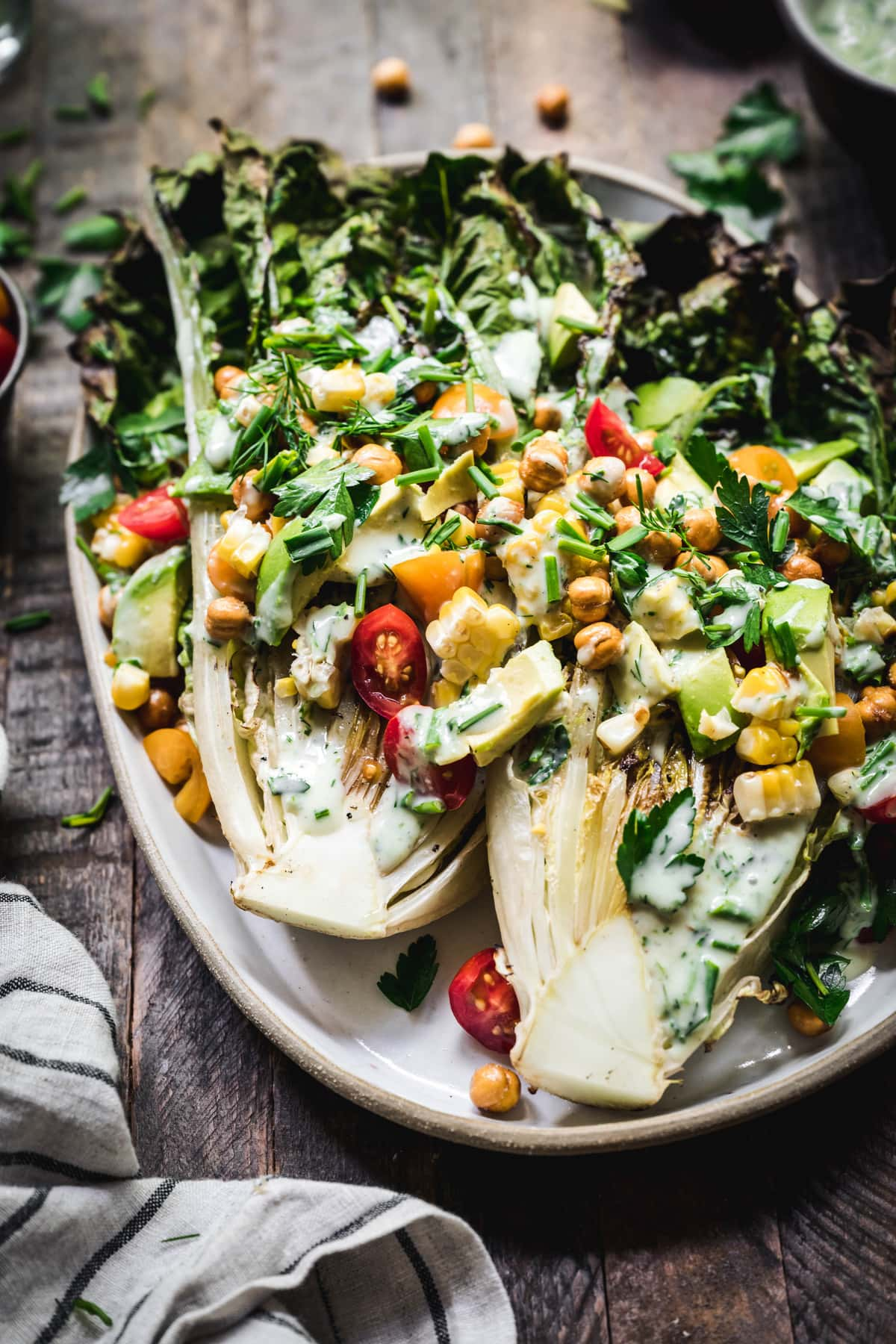 45 degree angle of grilled romaine salad with crispy chickpeas, vegan ranch and grilled corn on an oval platter