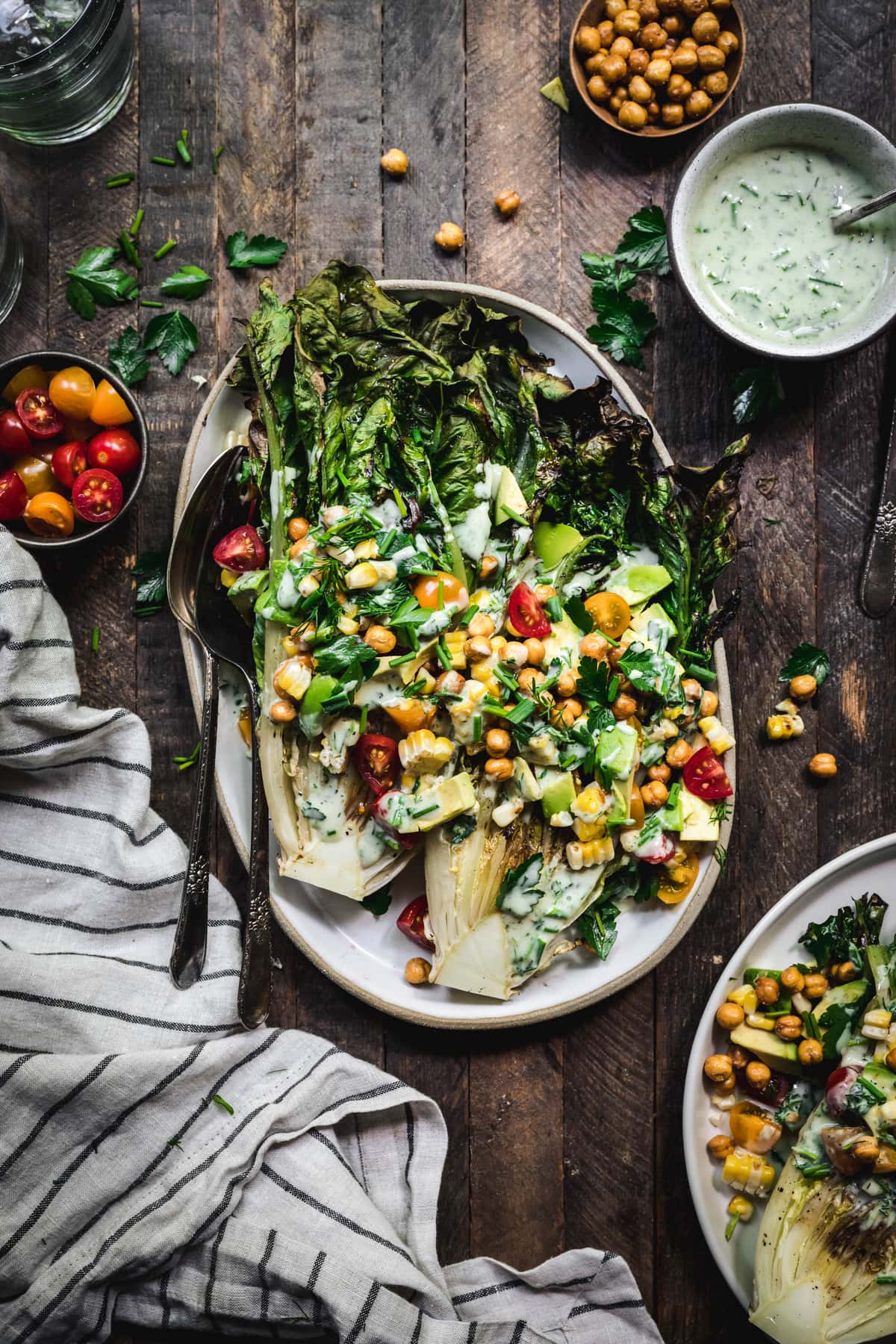 Overhead of grilled romaine salad with grilled corn, avocado, tomato and crispy chickpeas