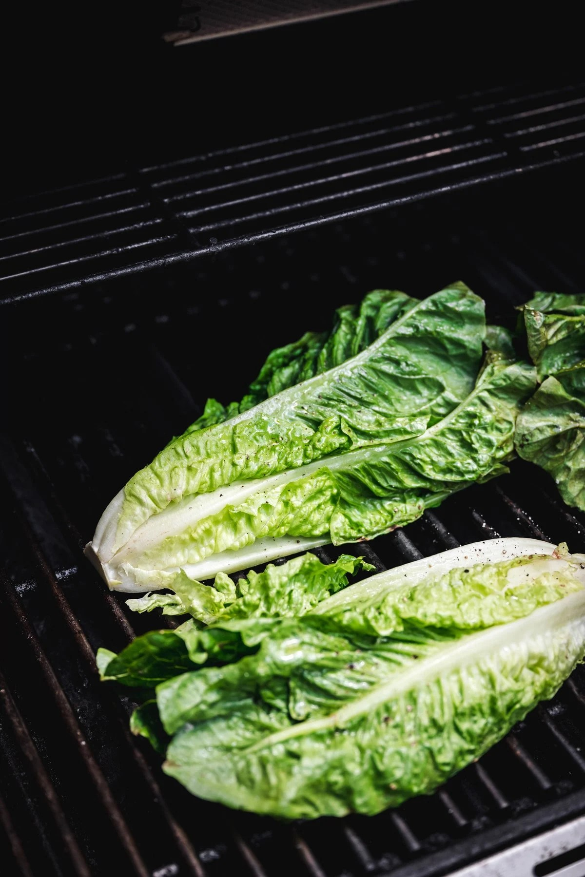 Two halves of a head of romaine lettuce on an open grill