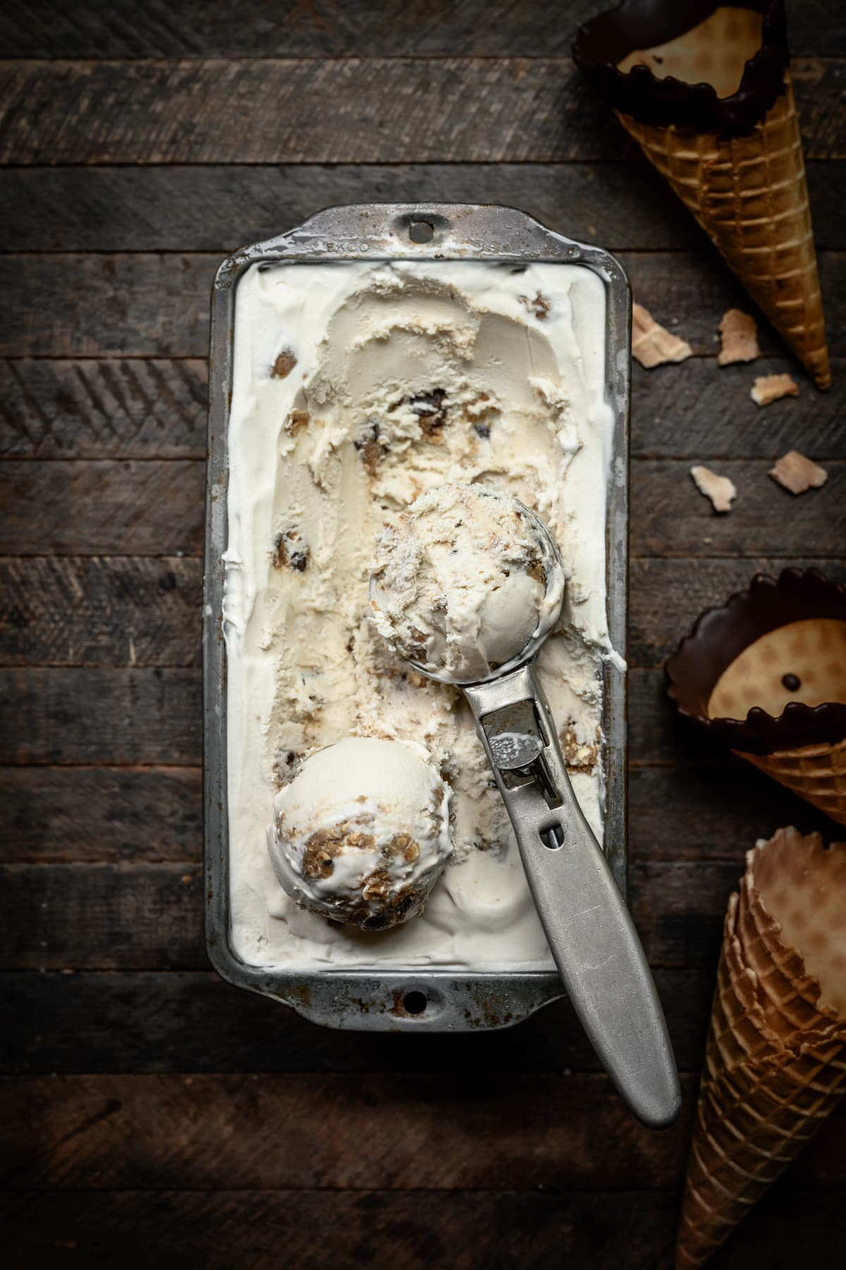 Overhead view of vegan cookie dough ice cream in antique pan with scoop