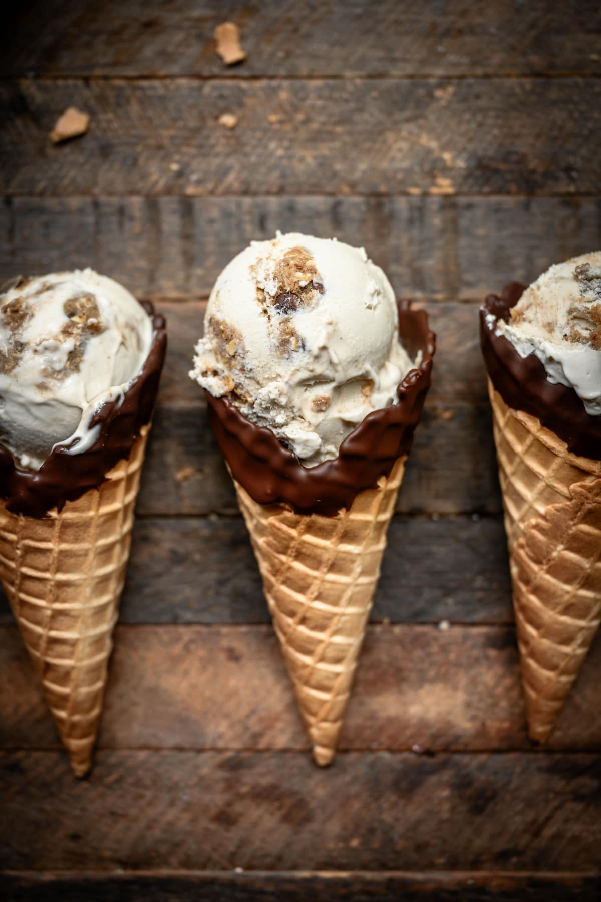 Overhead view of cookie dough ice cream in chocolate-dipped cones on wood background