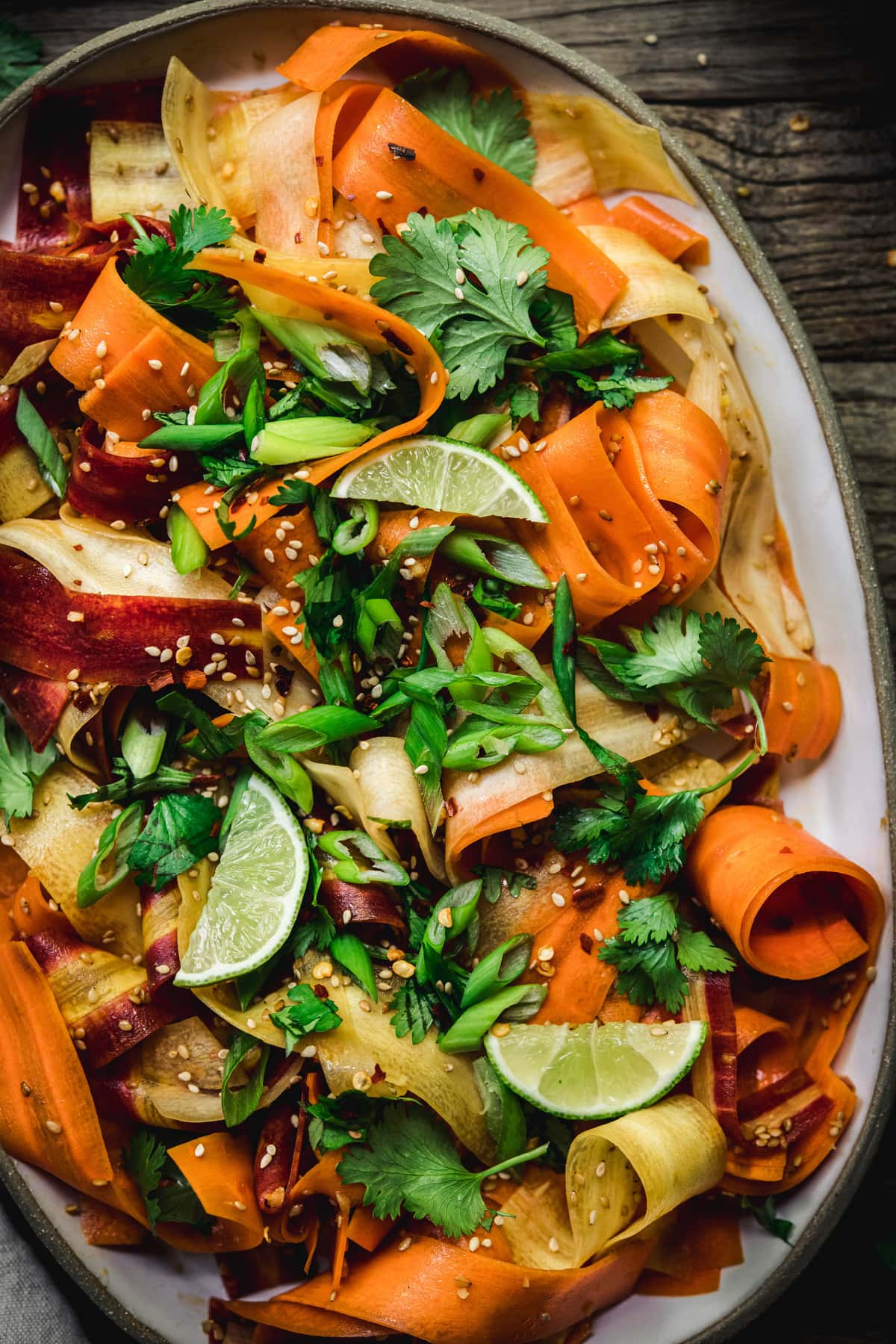 Close up Overhead view of shaved rainbow carrot salad on a platter on rustic wood table