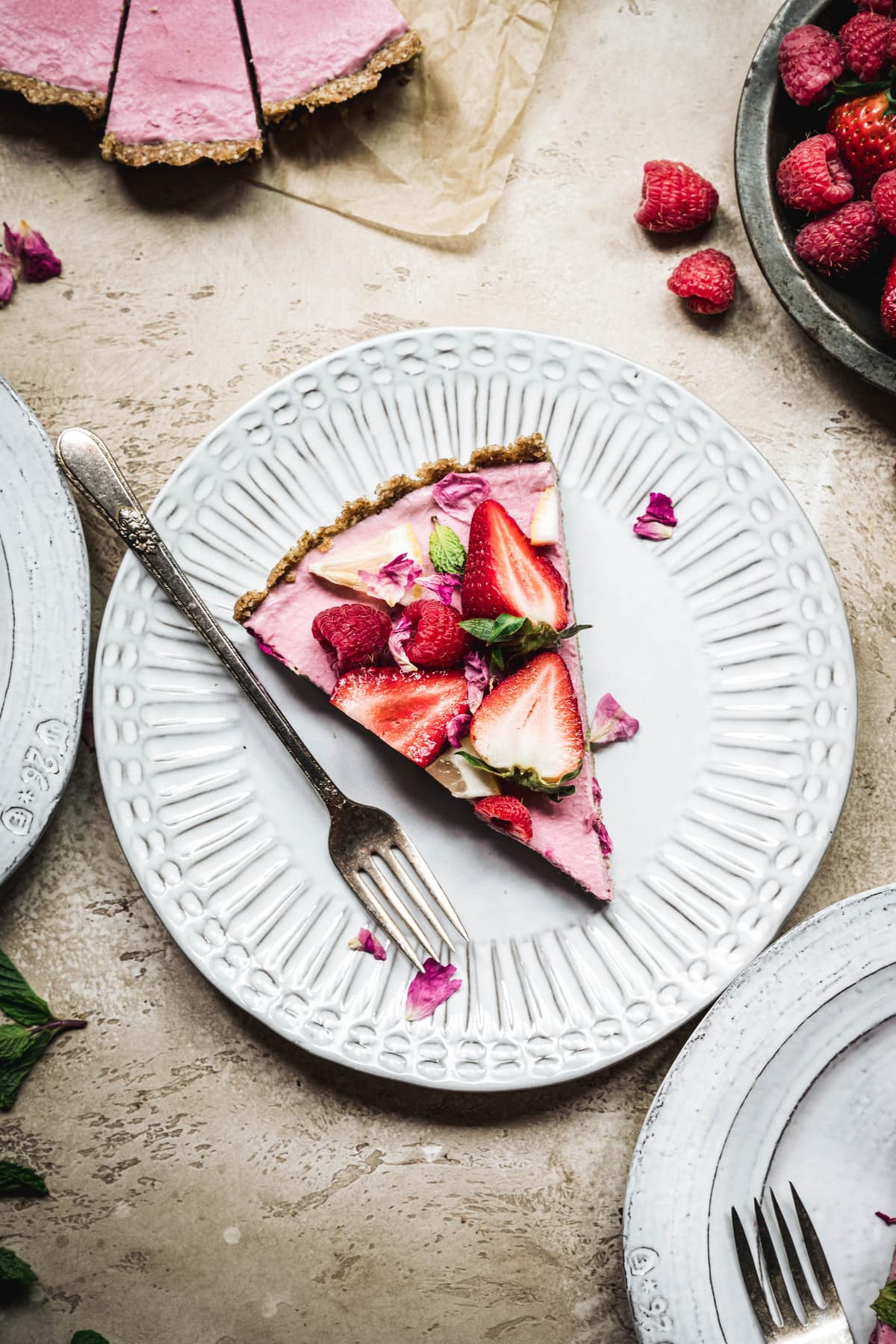 Overhead view of slice of vegan strawberry mousse pie on a white plate