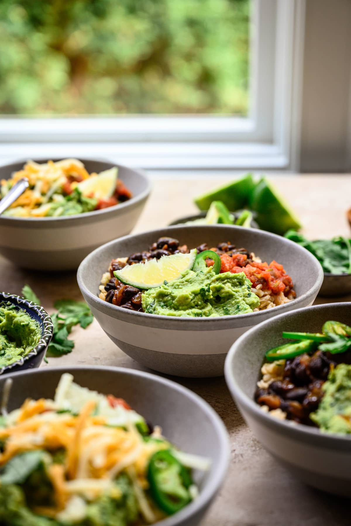 Side view of vegan burrito bowls with window in background