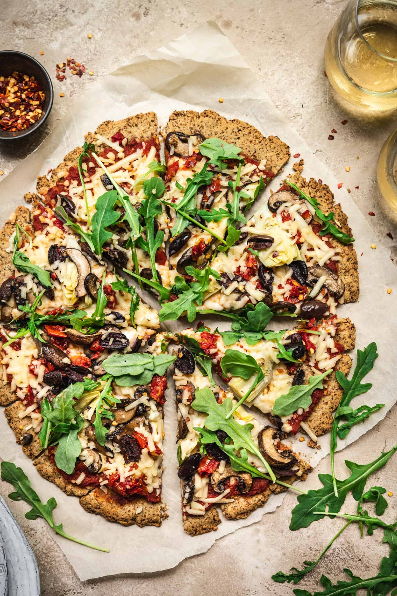 Overhead view of Crispy Cauliflower Vegan Pizza Crust with vegan pizza toppings on rustic background with white wine