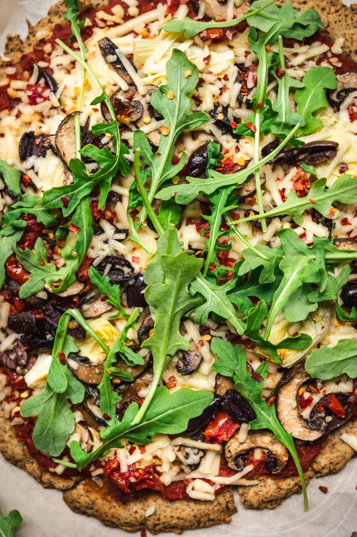Close up view of pizza with mushrooms, arugula, artichokes and olives
