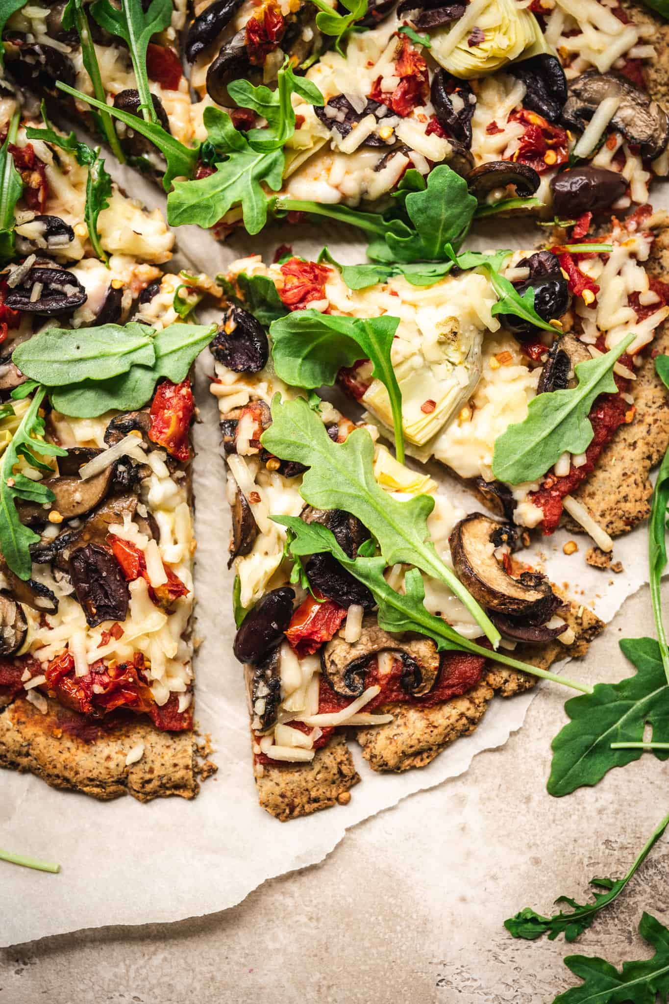 Close up overhead of a slice of pizza with vegan cauliflower crust and toppings