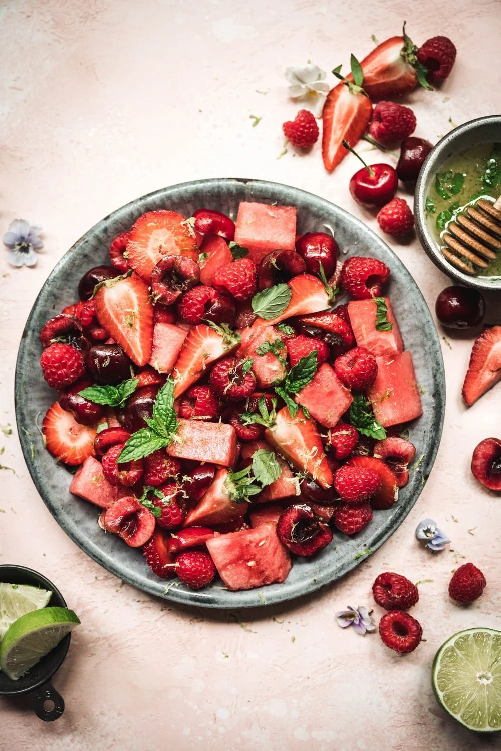 Overhead of watermelon berry salad with mint lime dressing in a blue bowl