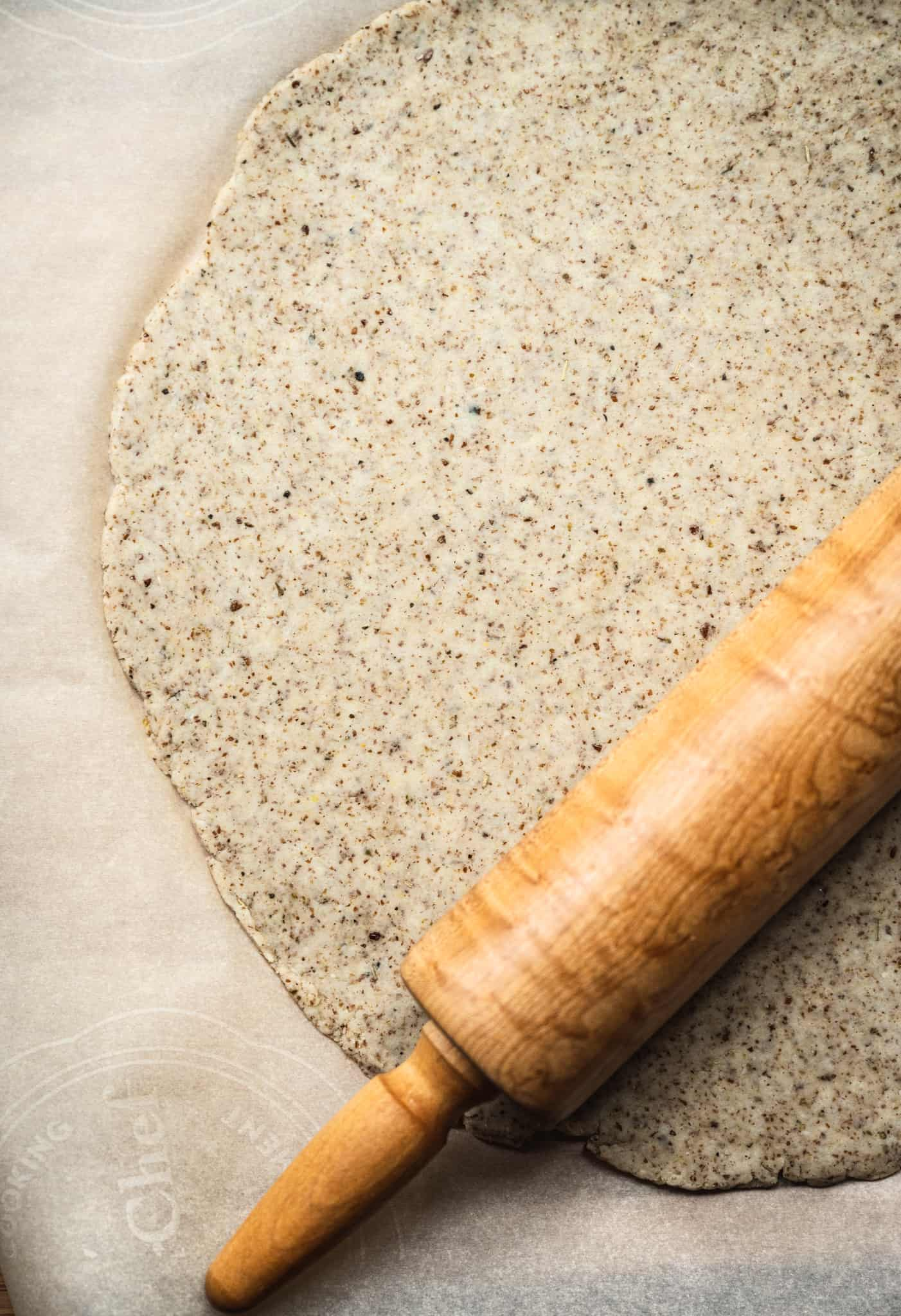 Overhead view of pizza crust being rolled out with rolling pin on parchment paper