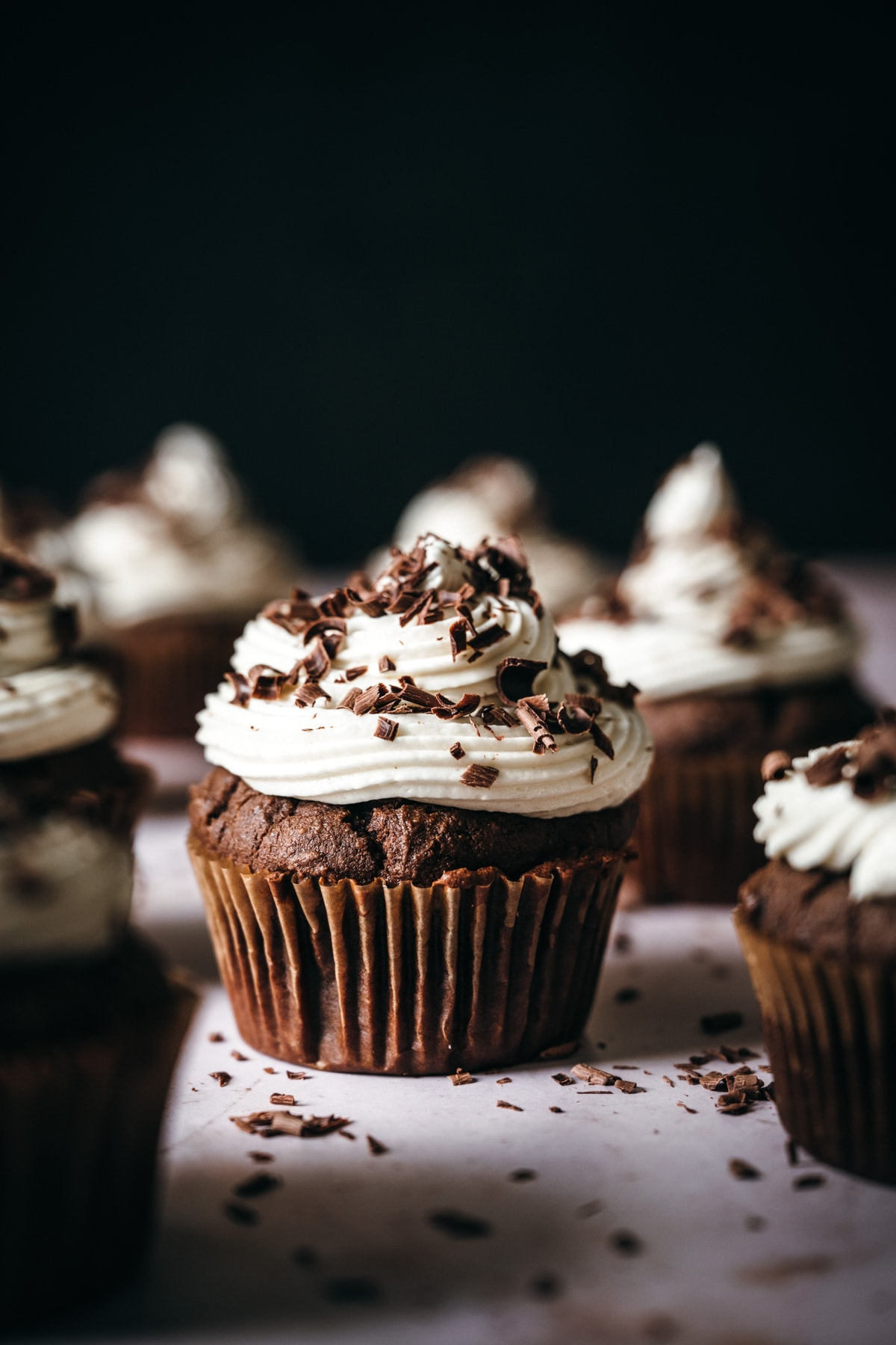 close up side view of vegan chocolate cupcake topped with vanilla frosting and chocolate shavings.