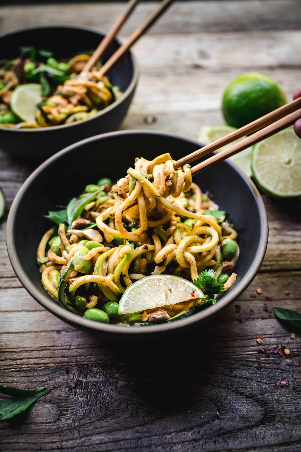 45 degree angle of red curry almond butter zucchini noodles in a bowl with chocpsticks