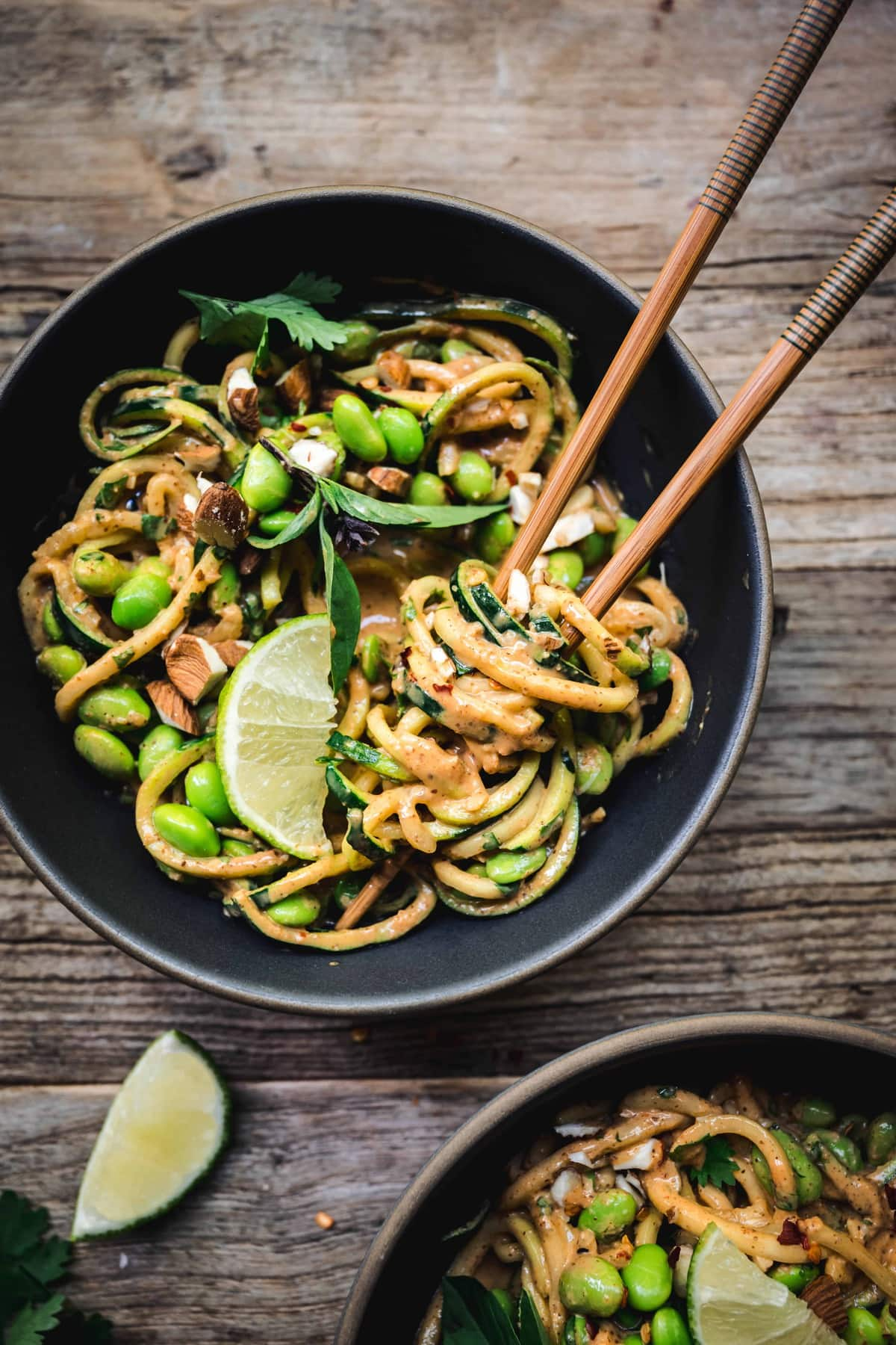 Overhead of red curry almond butter zucchini noodles in a bowl with chocpsticks