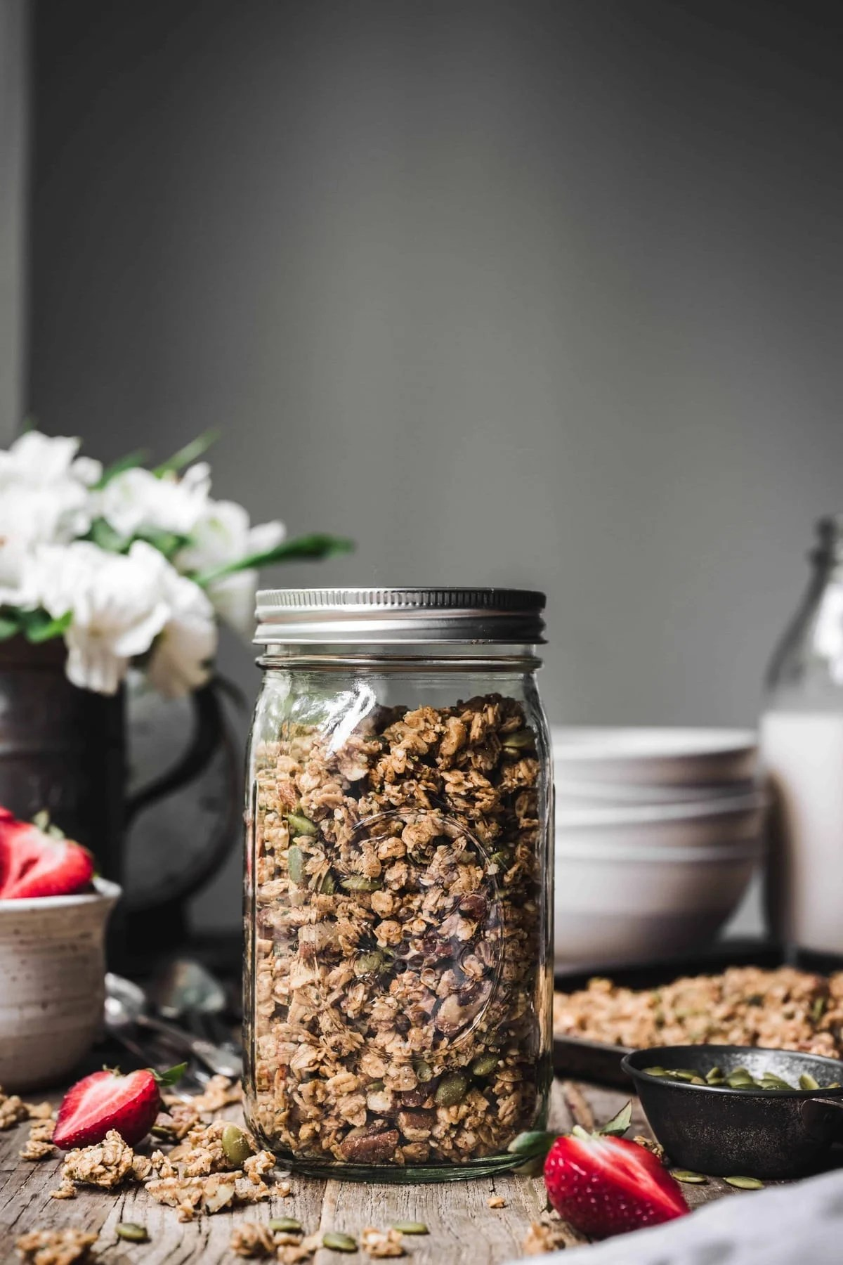 Side view of homemade granola in a glass jar on wood table