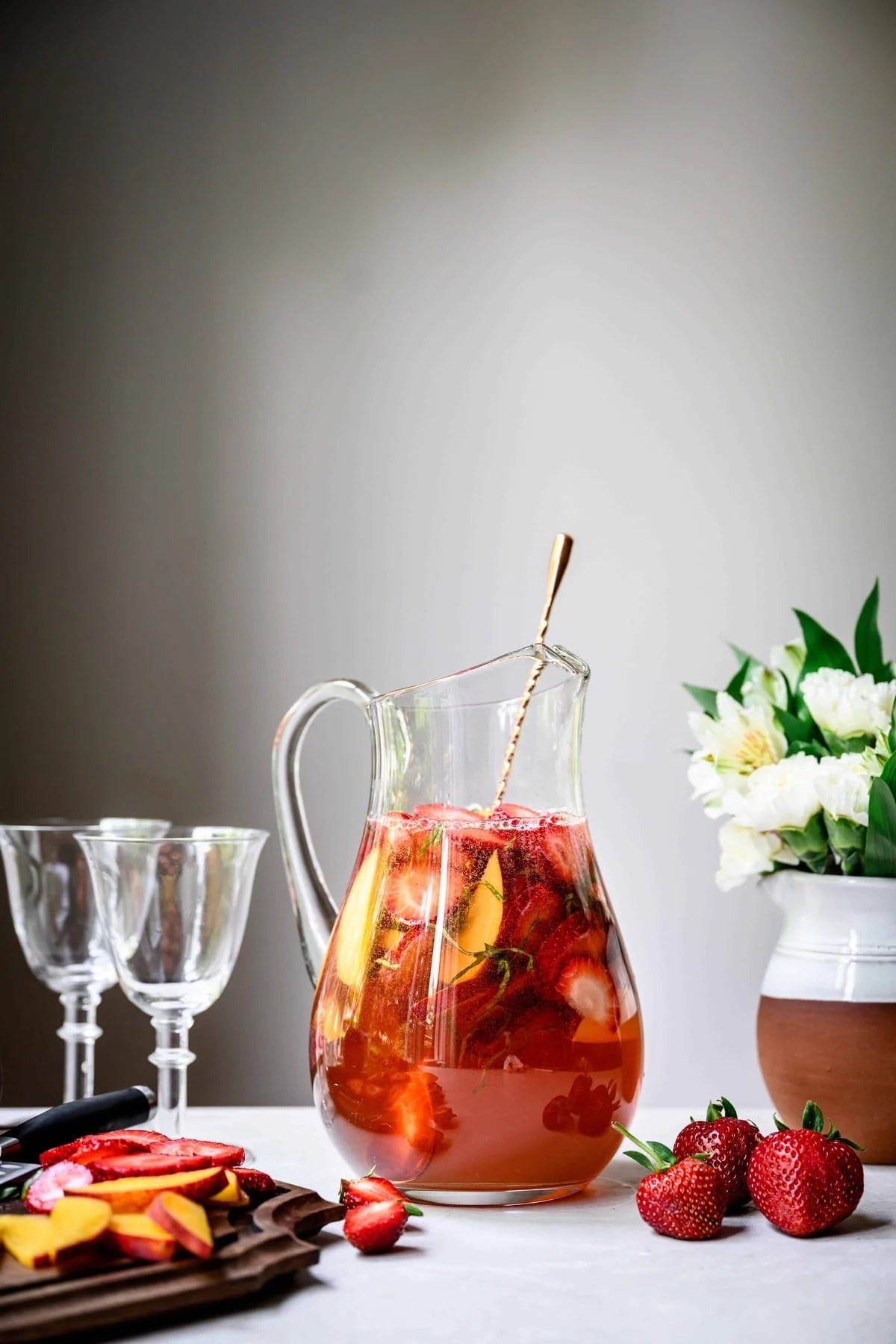side view of strawberry peach basil white wine sangria on white background