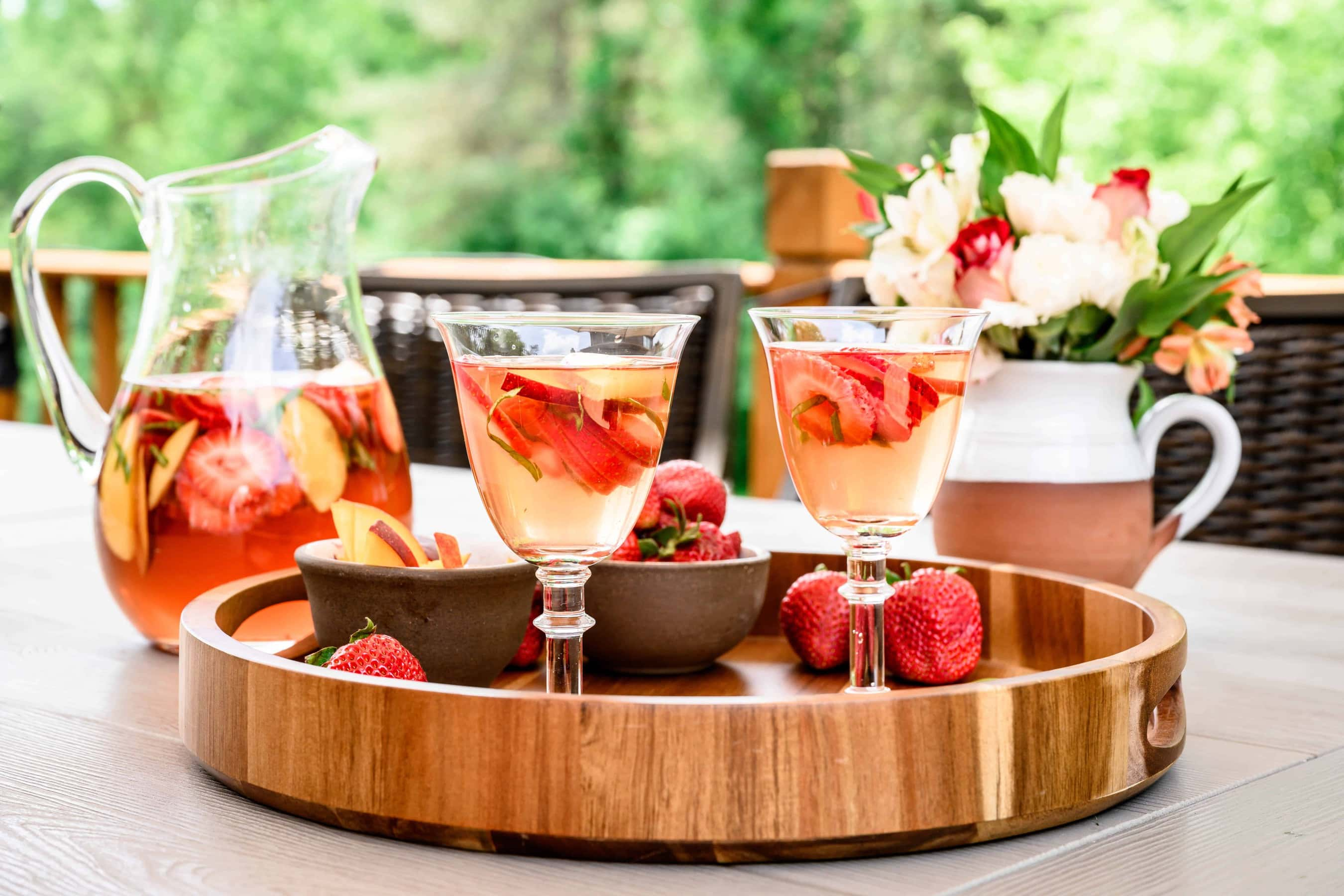 Side view of summer sangria in cocktail glasses on wood tray
