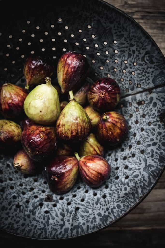 Overhead view of fresh, whole figs in colander