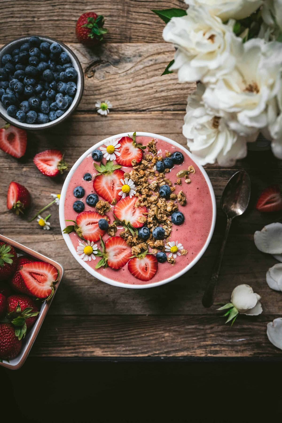 Overhead view of strawberries and cream smoothie bowl with fresh berries and granola on wood table