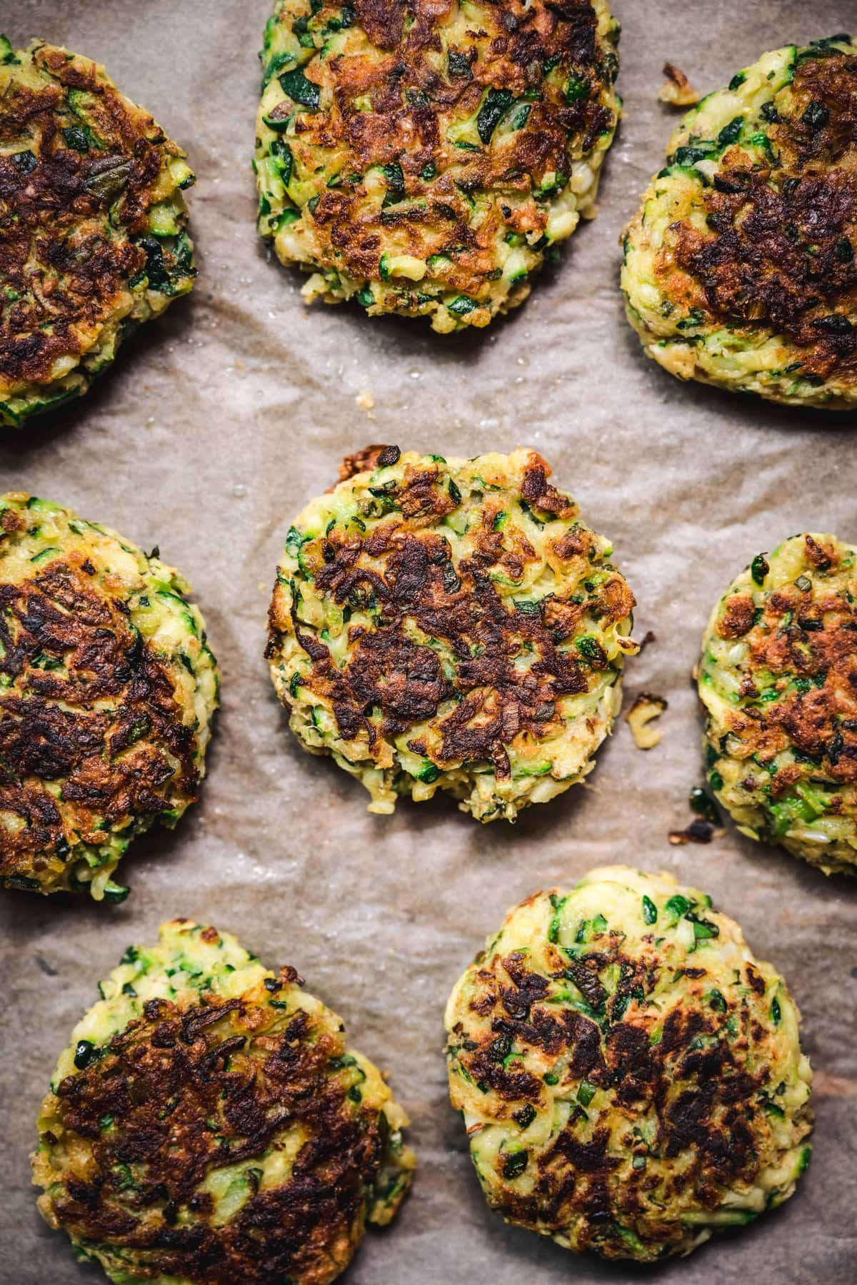 overhead of gluten free zucchini fritters on parchment after they're pan fried