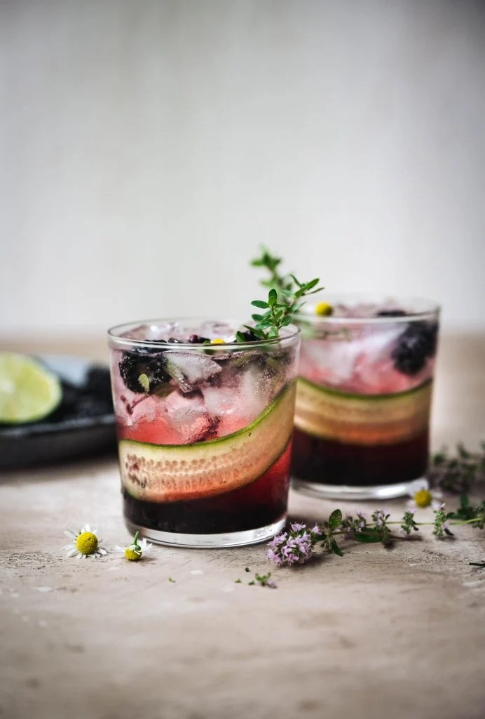 side view of two blackberry cucumber gin cocktails with fresh herb garnish