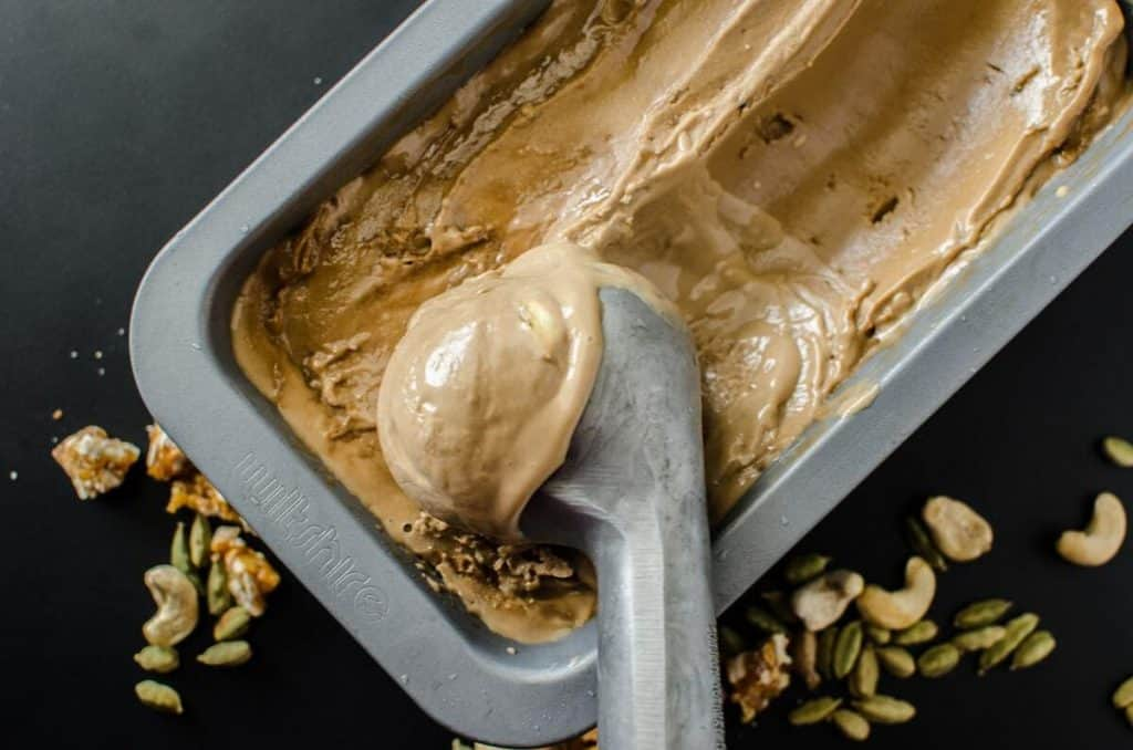 overhead of vegan caradmom spiced coconut ice cream in a tin with a scoop