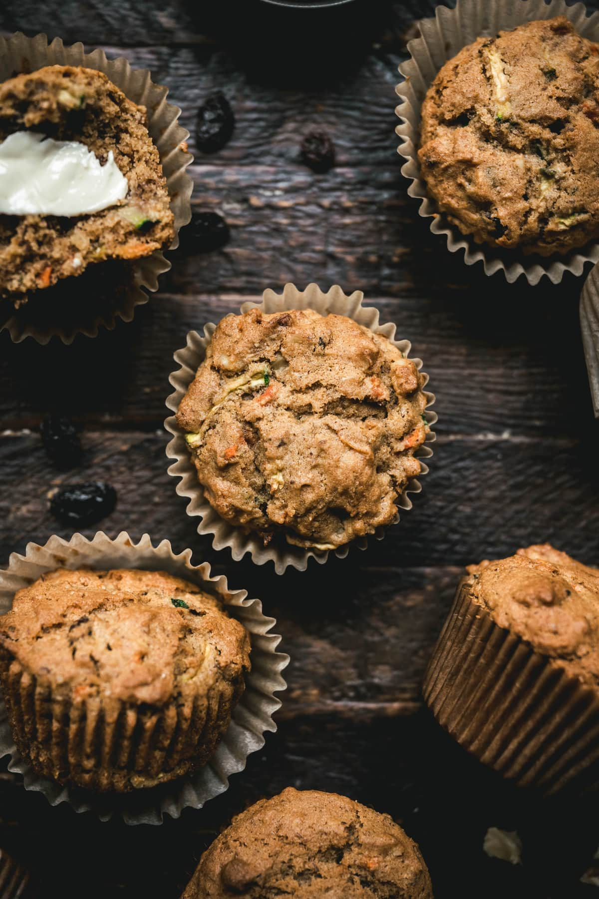 overhead of several gluten free vegan carrot zucchini muffins in liners on a dark wood background