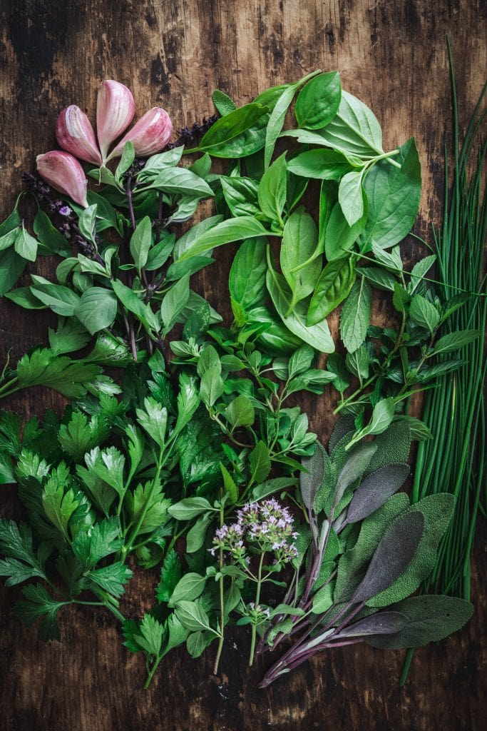 overead of a mixture of fresh herbs on a wooden background