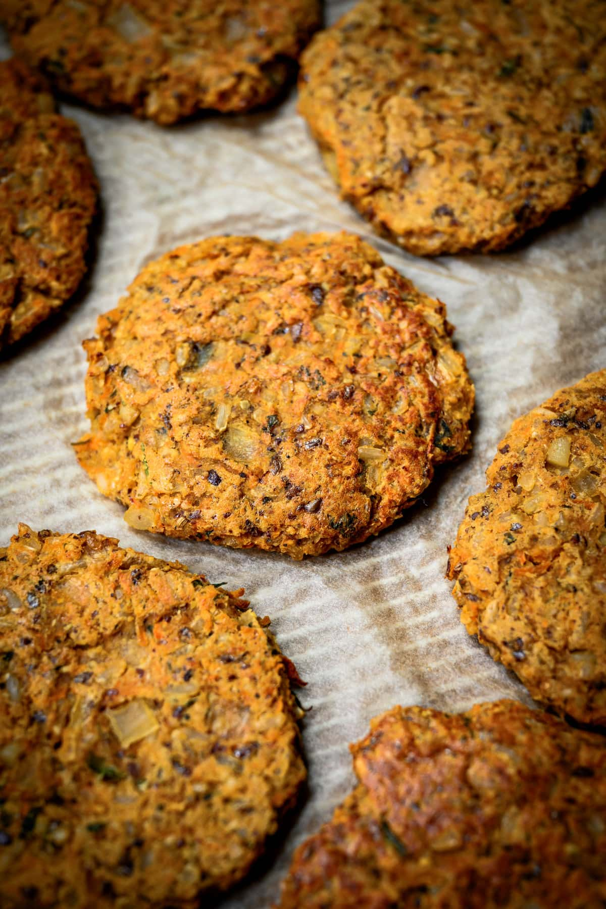 side view of cooked indian-spiced veggie burgers on parchment paper