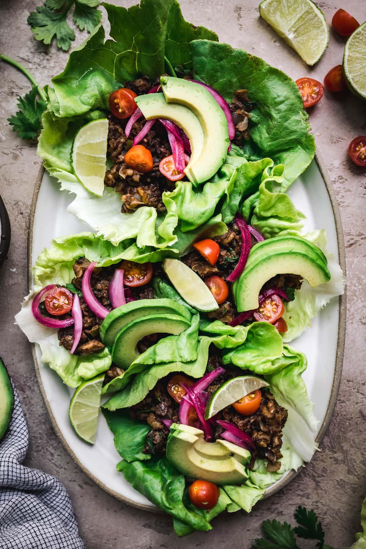 overhead of vegan lentil taco lettuce wraps on an oval platter