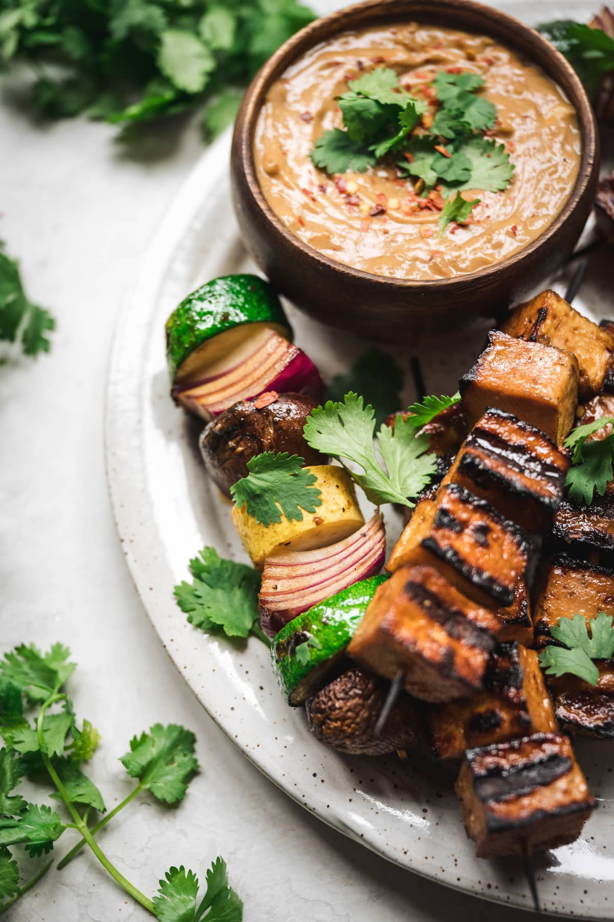 overhead of vegan peanut dipping sauce with tofu and vegetable kebabs