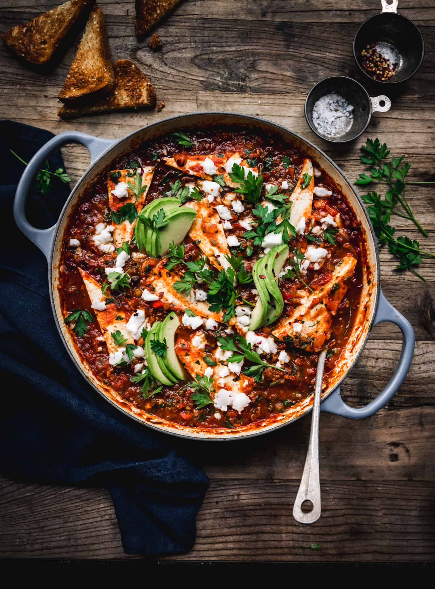 overhead of vegan shakshuka in a round baking dish with a spoon