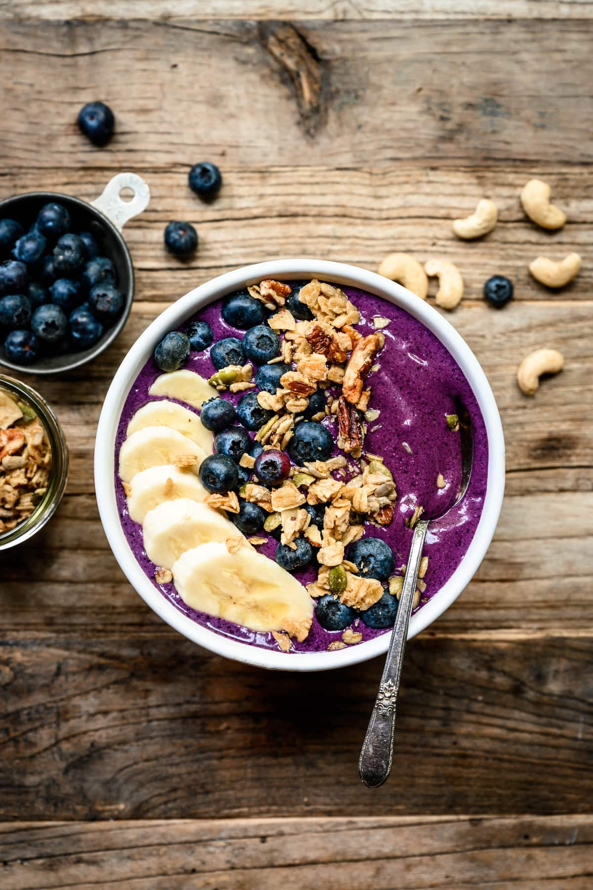 overhead of blueberry recovery smoothie bowl with banana, almond butter and granola