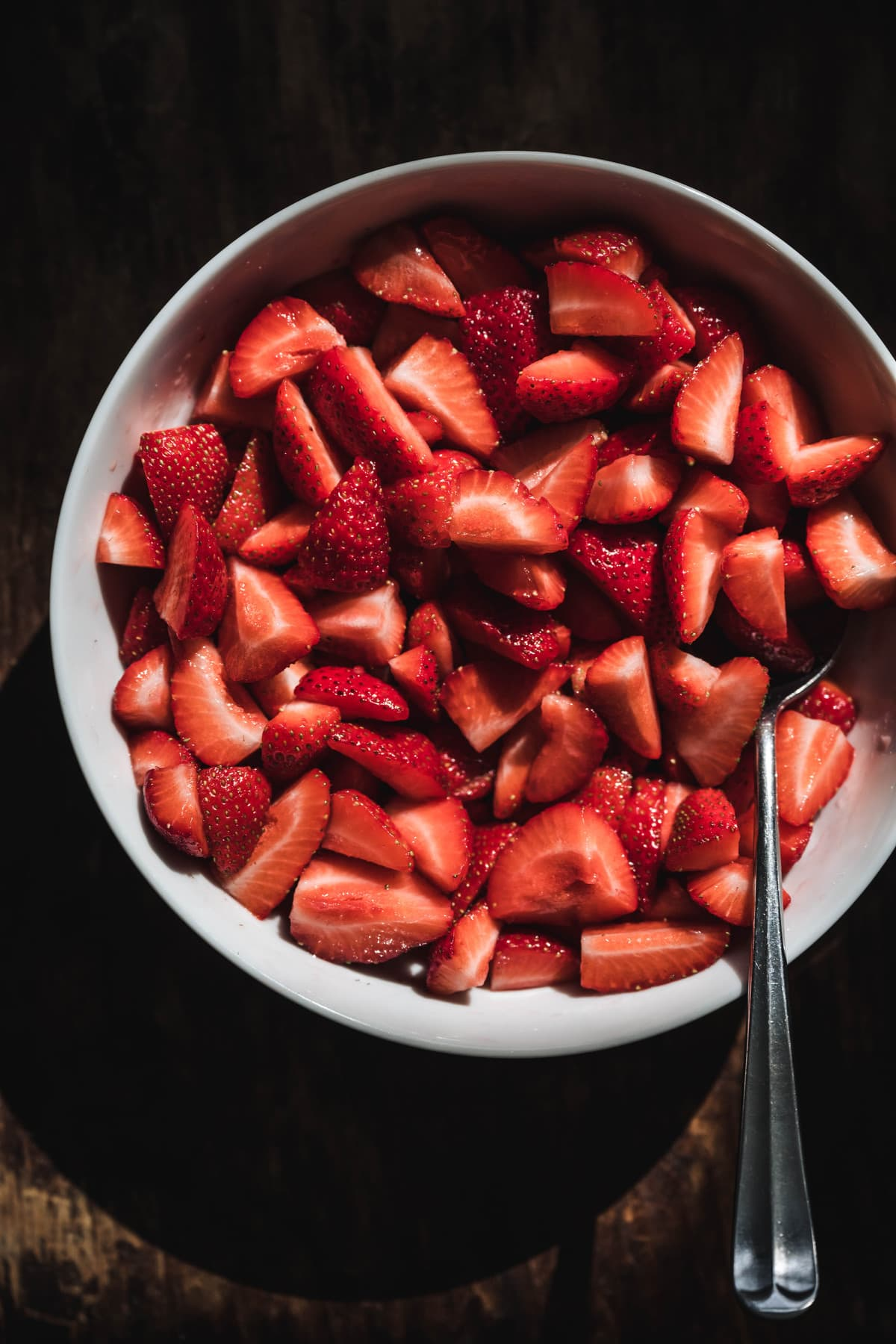 overhead of fresh sliced strawberries in a bowl