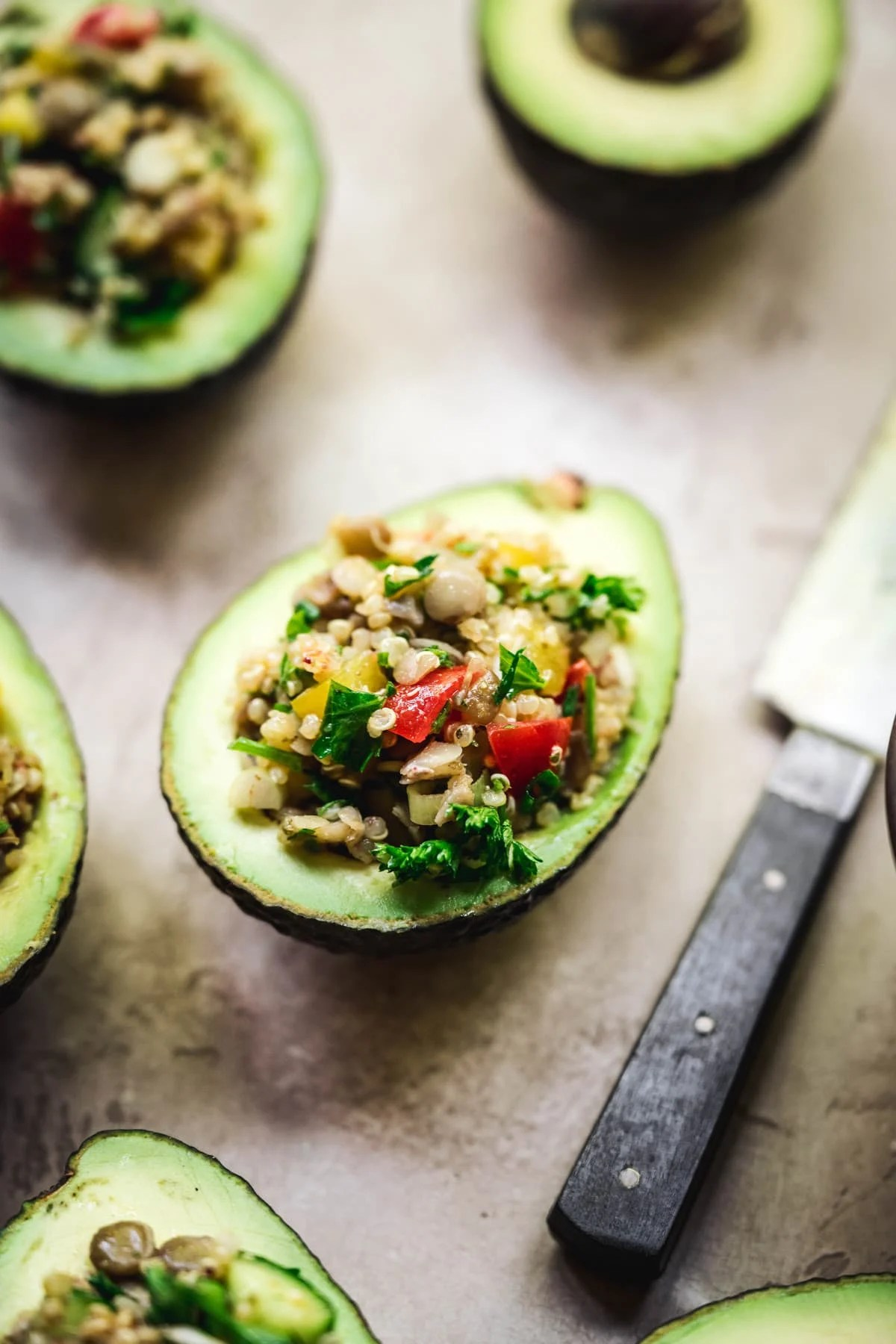 side view of vegan stuffed avocados with easy tahini dressing
