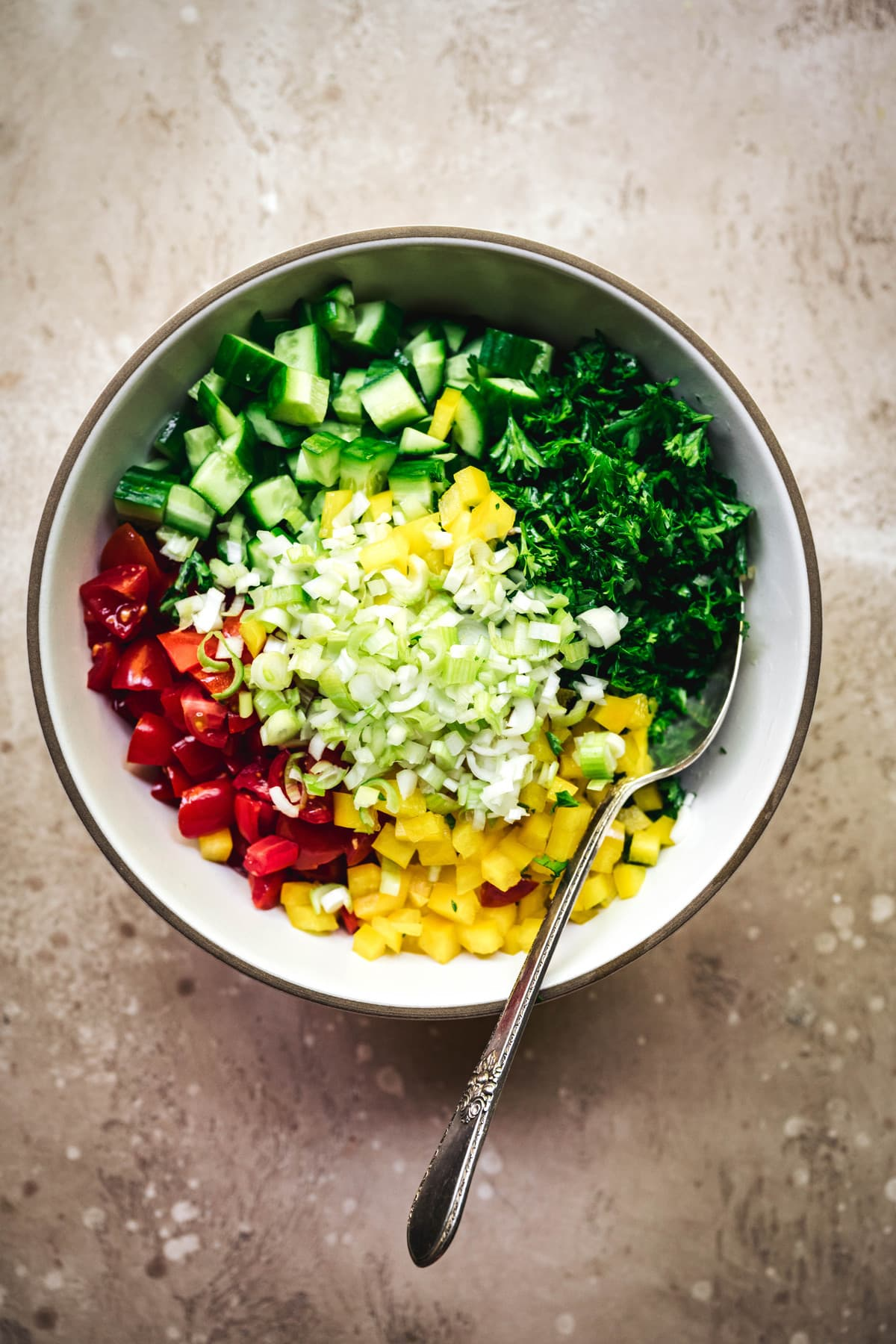 overhead view of diced vegetables in a bowl to make mediterranean stuffed avocados