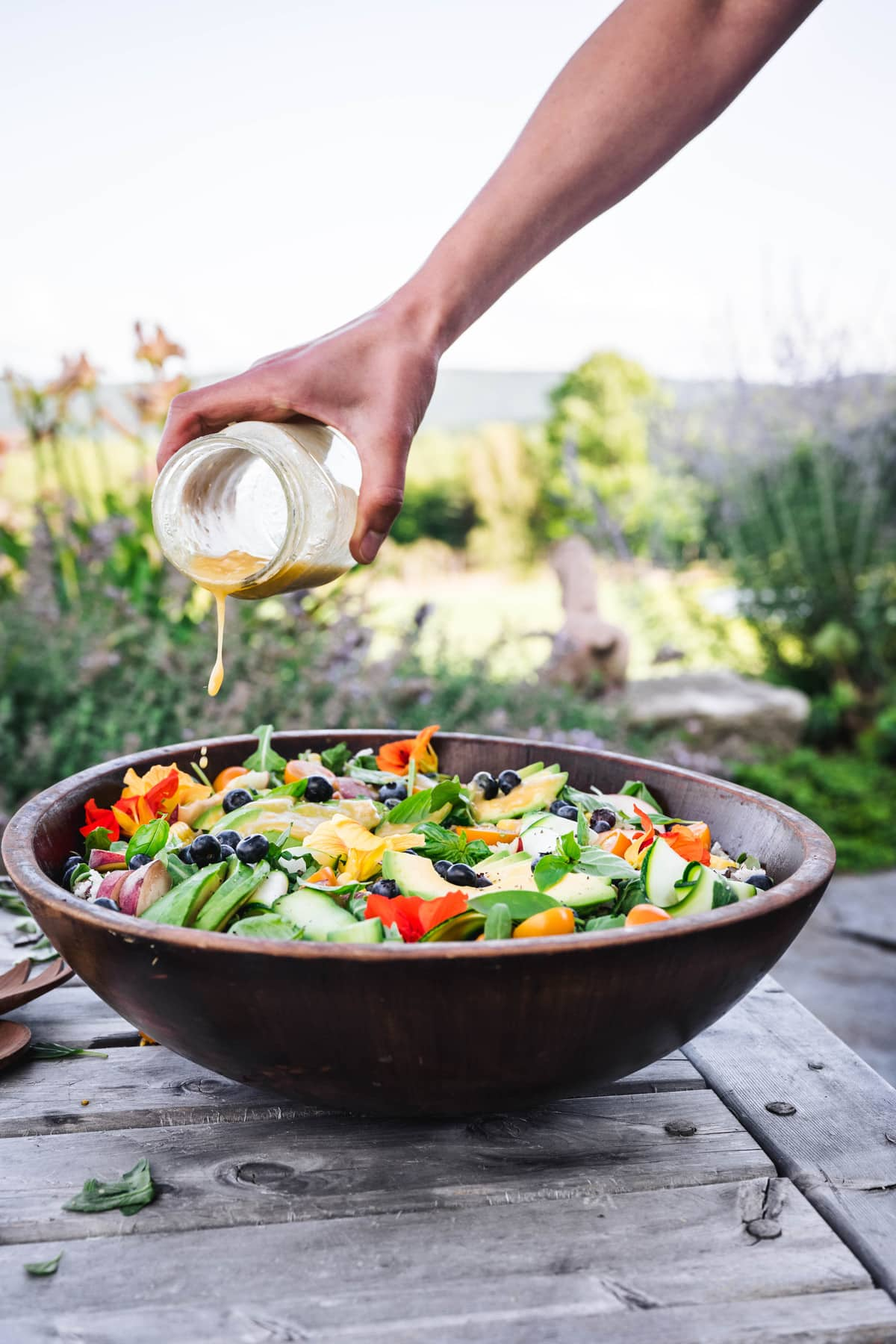 side view of someone pouring vinaigrette over summer grain salad in a wooden serving bowl with green field in the background