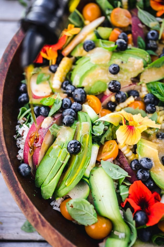 overhead closeup of summer grain salad with avocado and blueberries in a wooden serving bowl