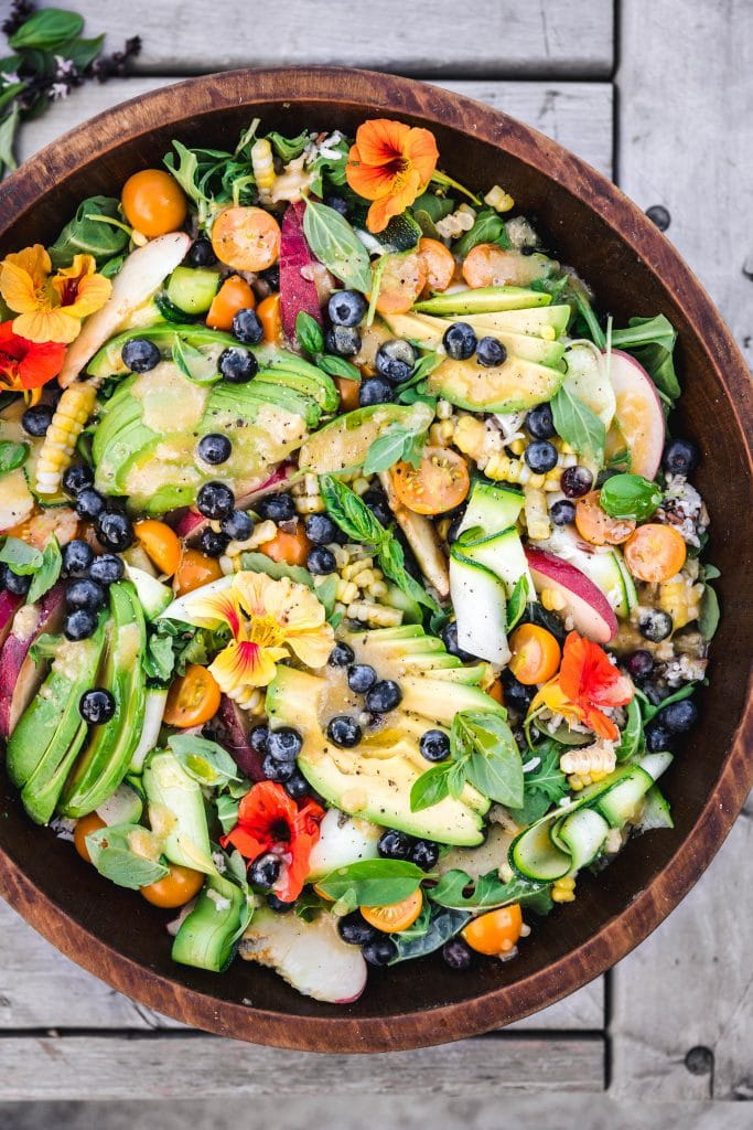 overhead of summer vegetable and wild rice salad with fresh herbs