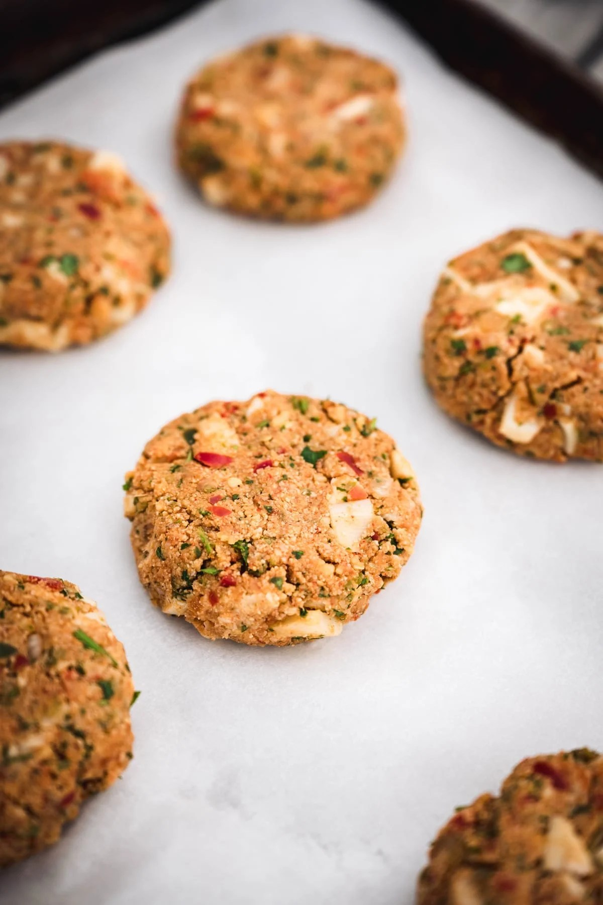45 degree angle of vegan crab cakes before they're cooked on a baking sheet