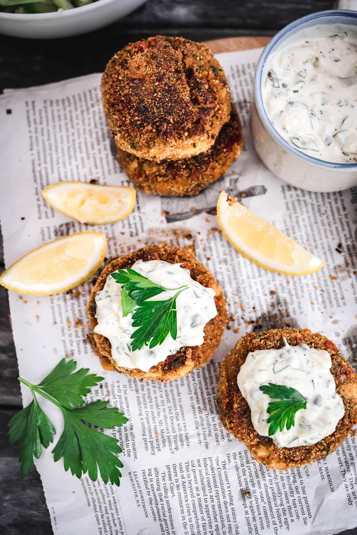 overhead of two vegan crab cakes with vegan tartar sauce on newspaper