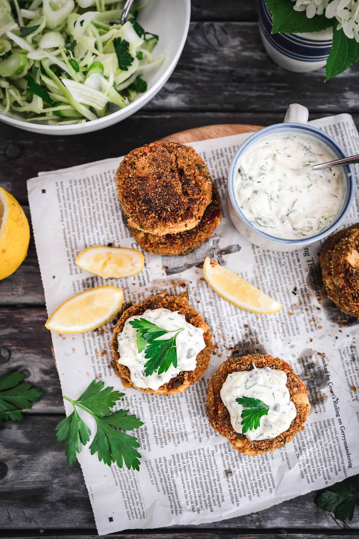 overhead of vegan crab cakes with vegan tartar sacue on newspaper and a fennel salad