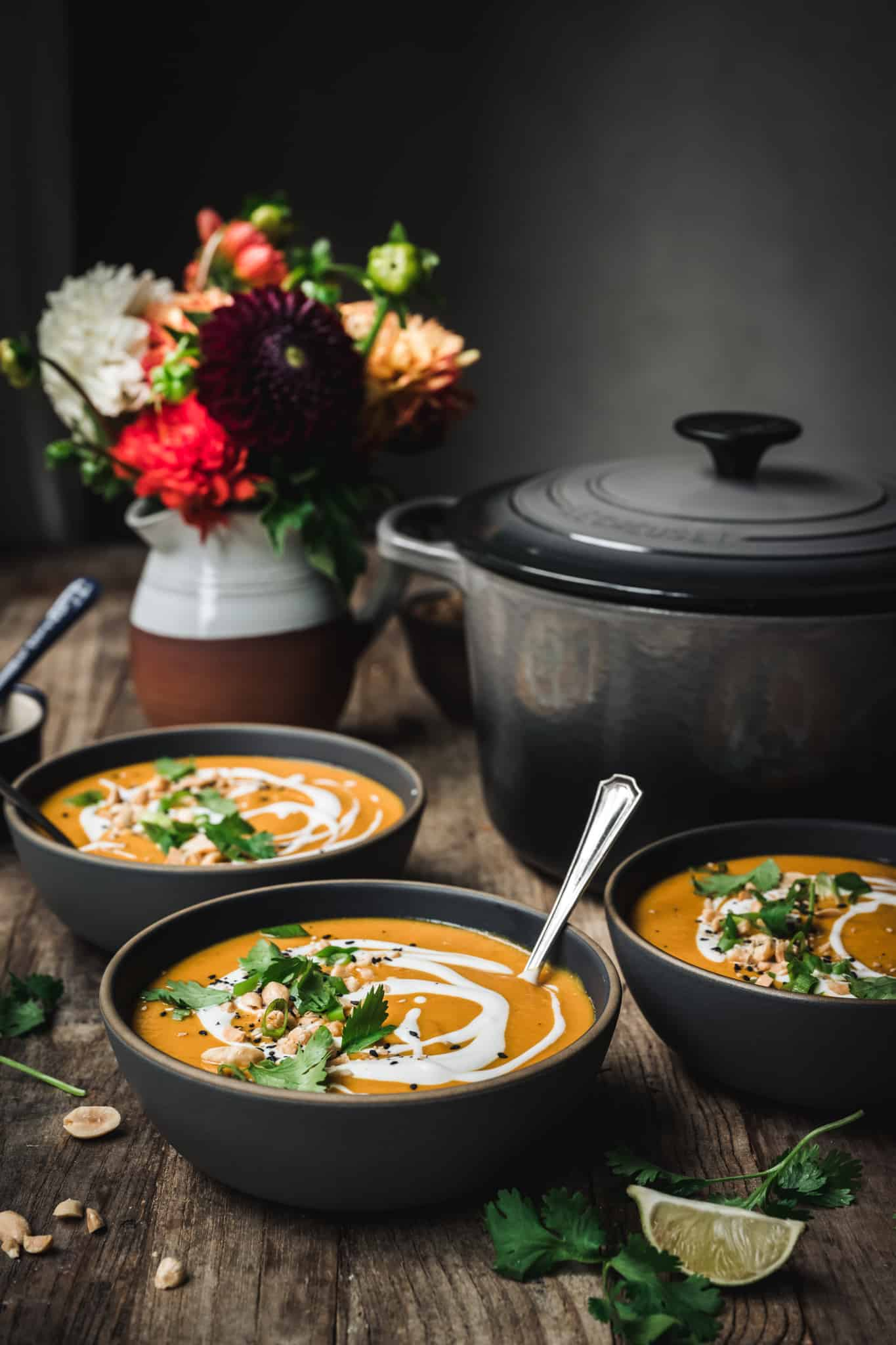 side view of three bowls of vegan coconut curry squash soup on wood table with fall flowers in background
