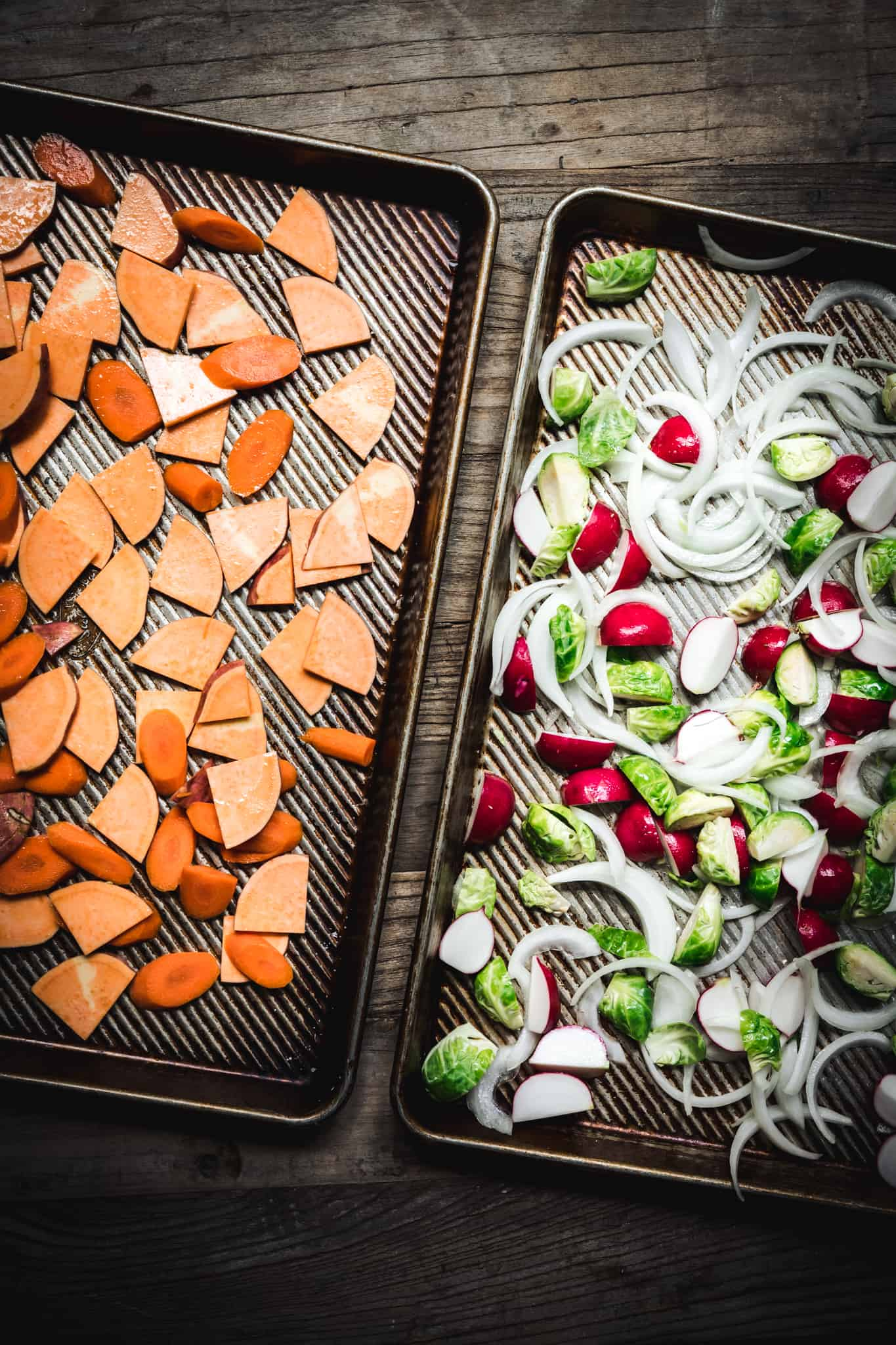 overhead of two sheetpans with different mixtures of fall vegetables to be roasted