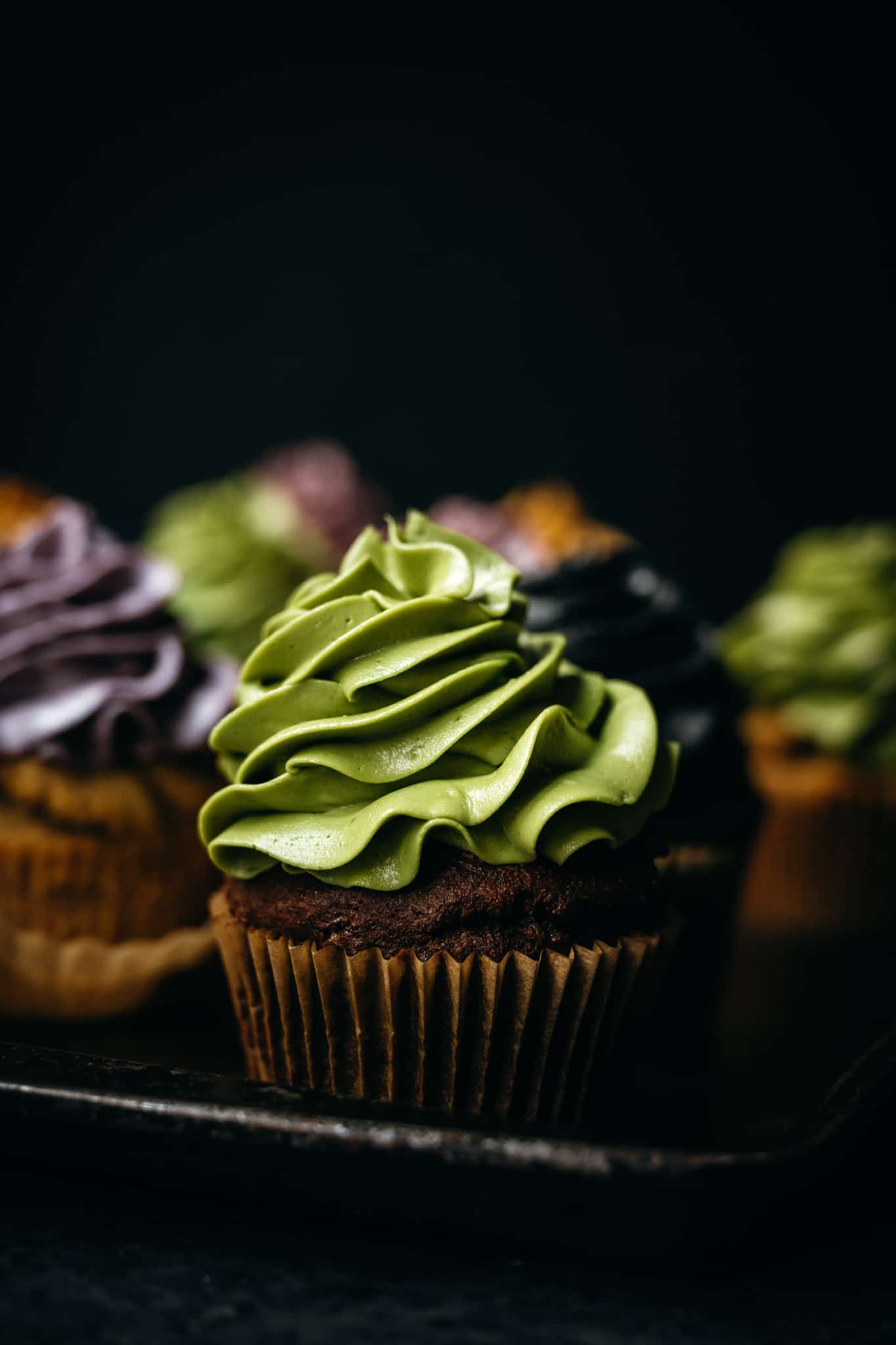 closeup side view of vegan chocolate cupcake with green frosting colored with matcha