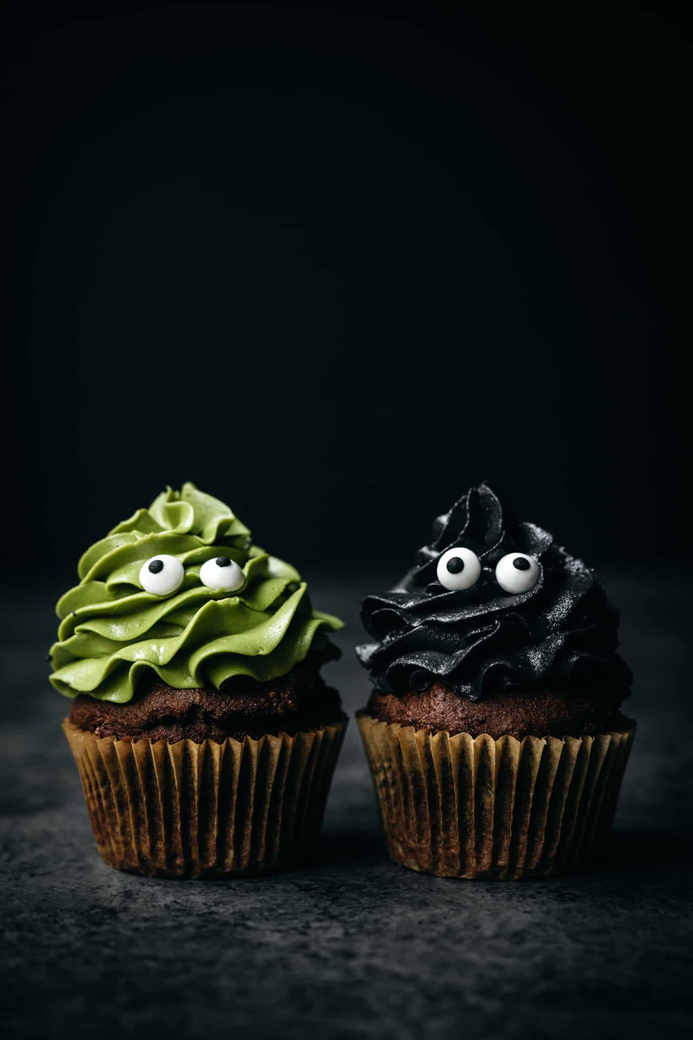 side view of two vegan chocolate cupcakes topped with naturally colored frosting in green and black from charcoal