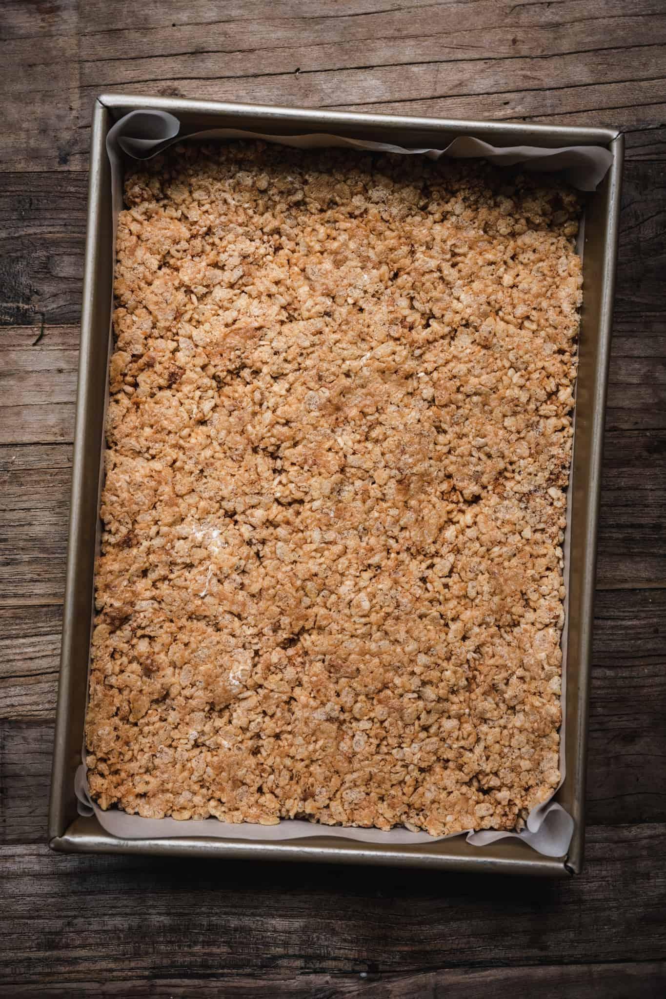 overhead of vegan peanut butter rice krispy dough pressed into a prepared baking dish