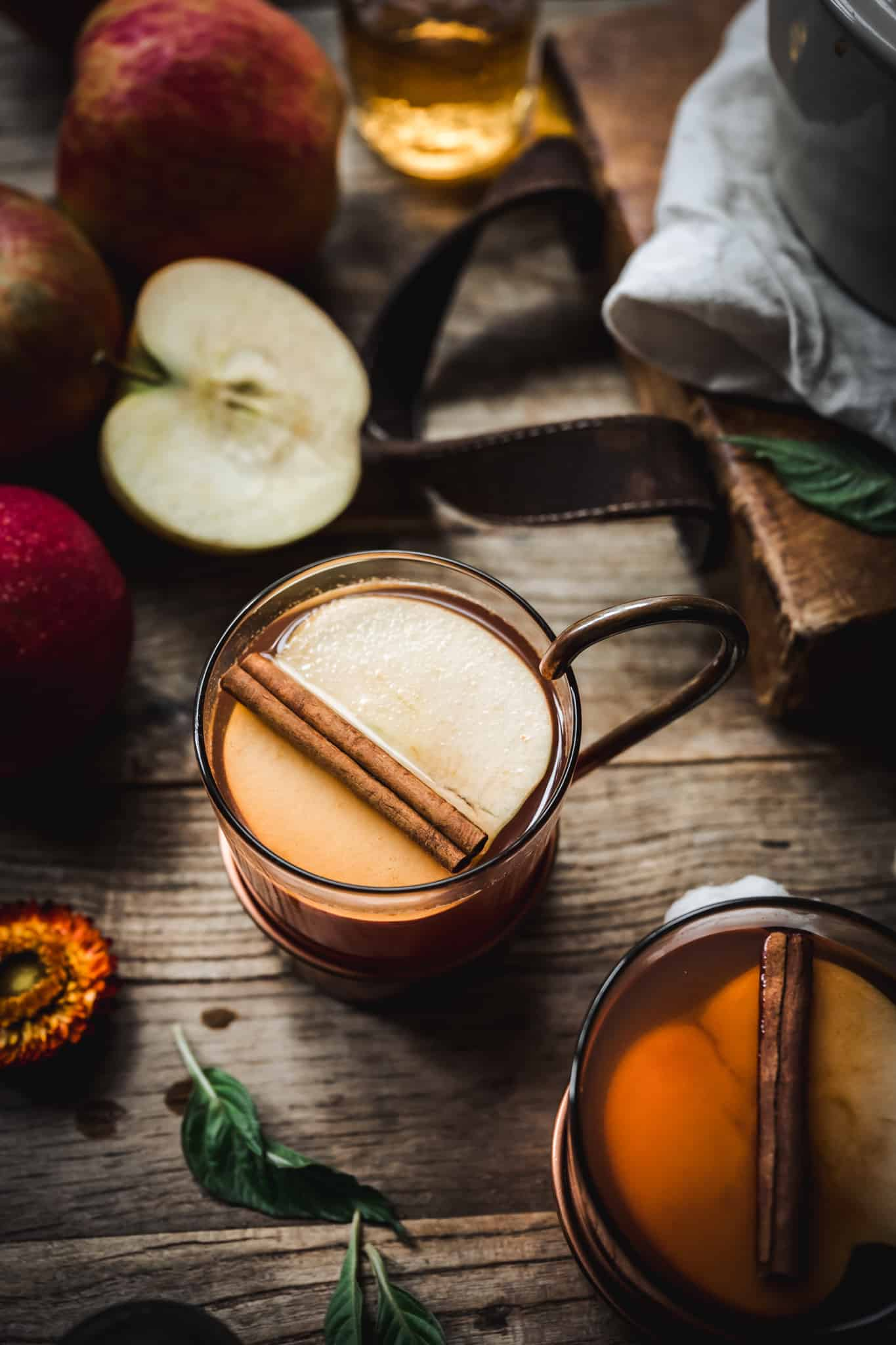 Overhead view of hot apple cider cocktail garnished with cinnamon stick on rustic wood background