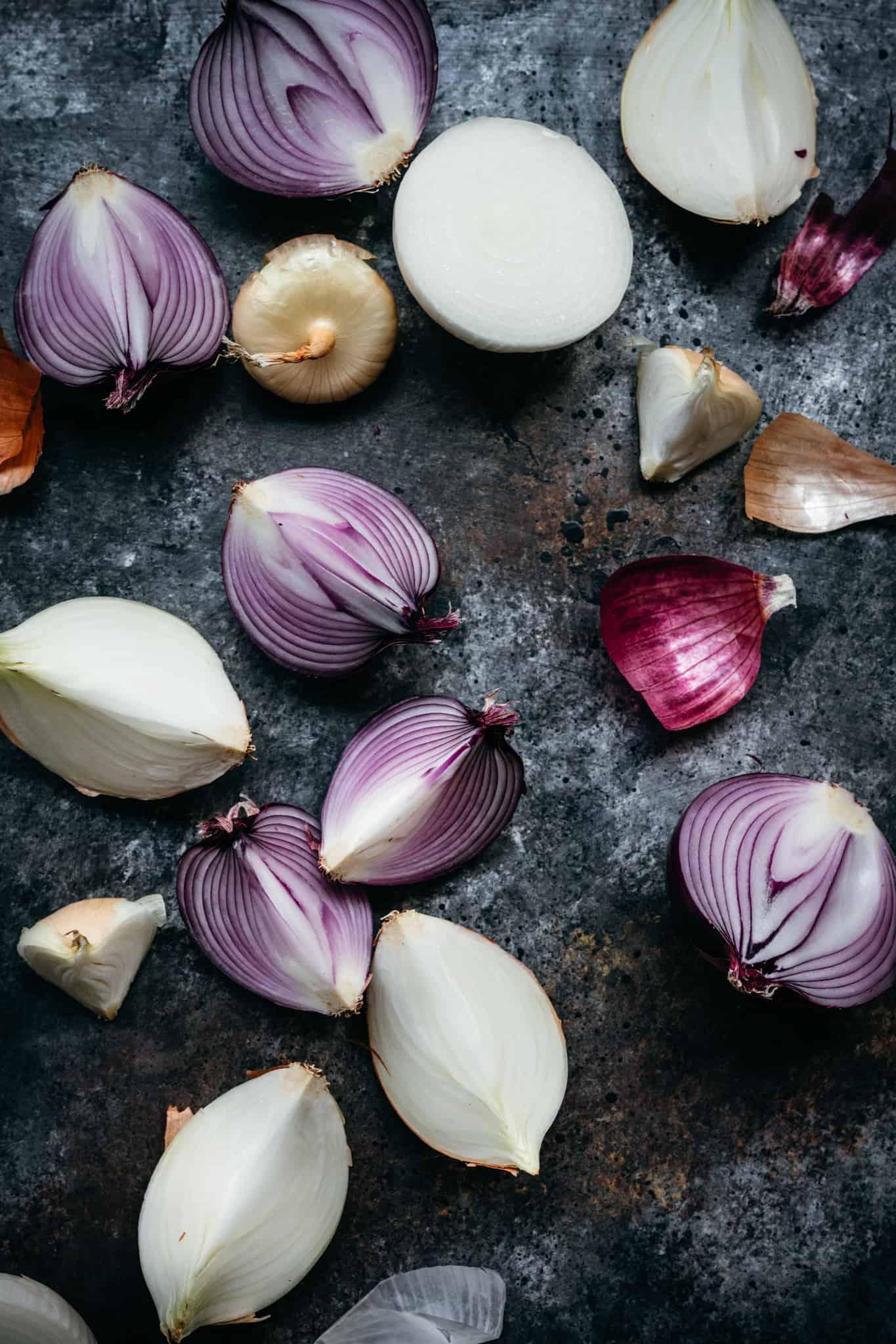overhead of fresh purple onions chopped on a black background