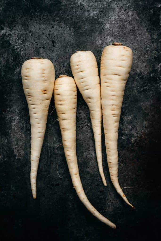 overhead of four white parsnips on a black background