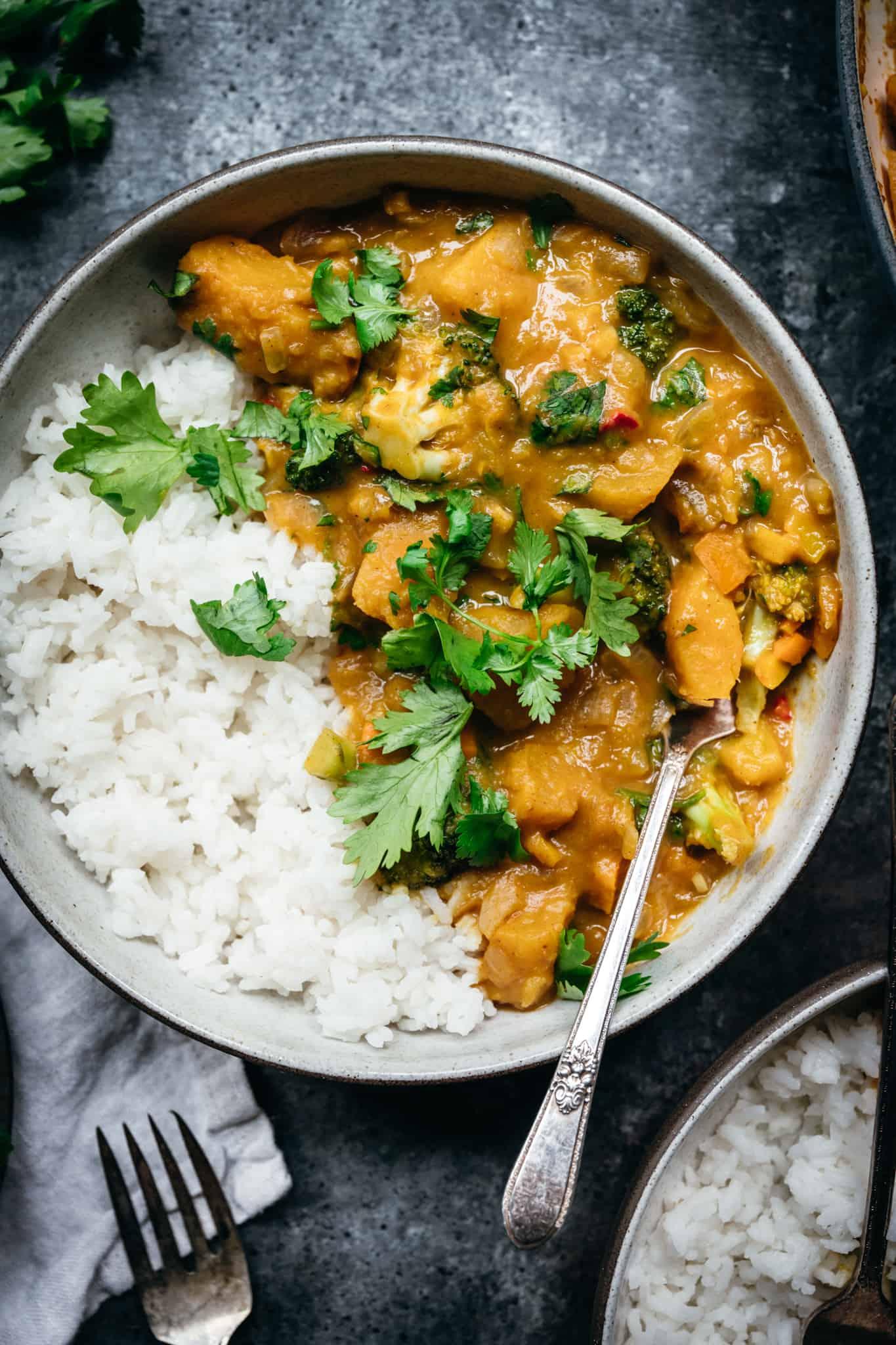 overhead of vegan pumpkin curry with steamed jasmine rice